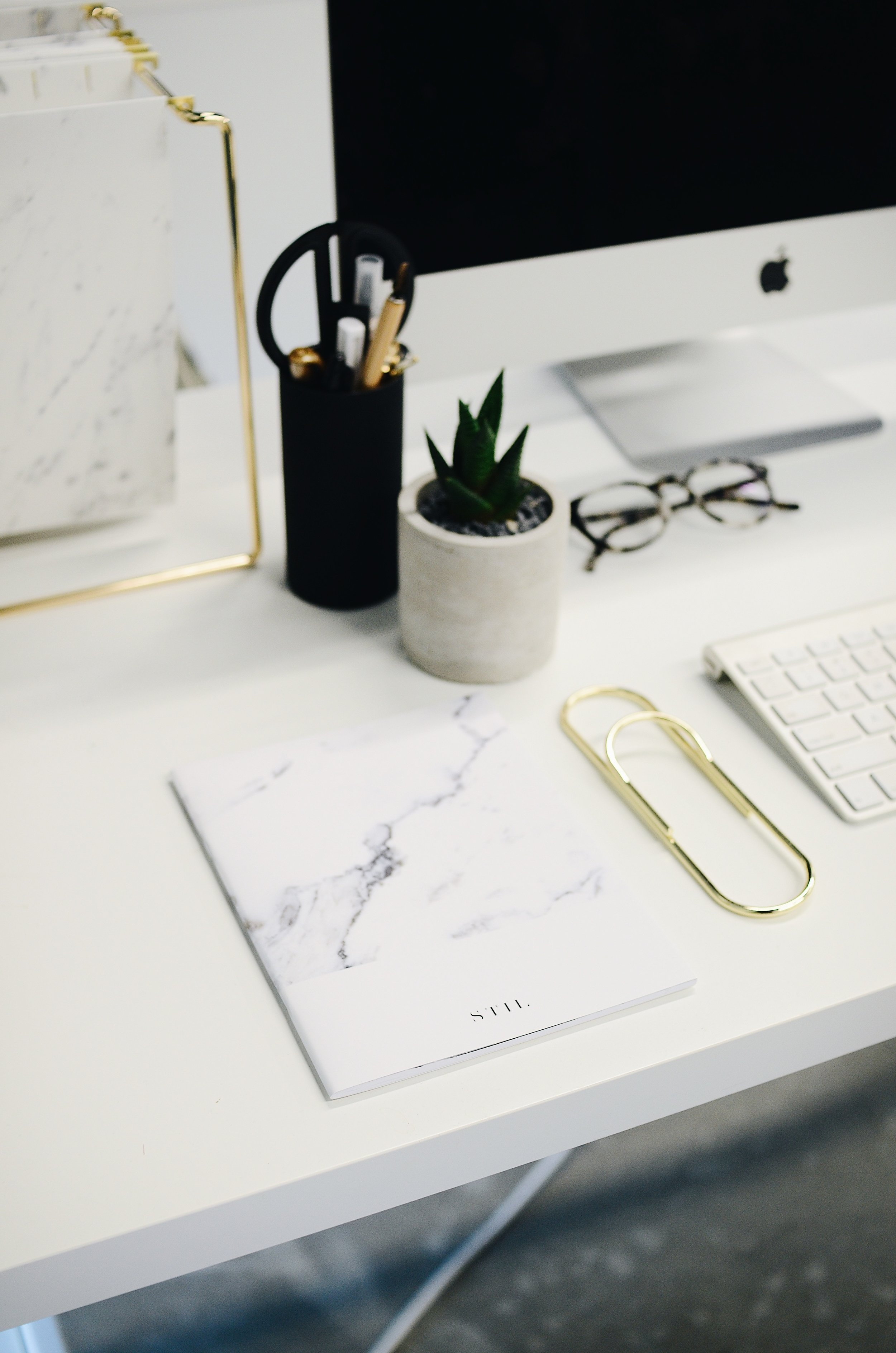 White notepad on a minimal desk with gold paperclip