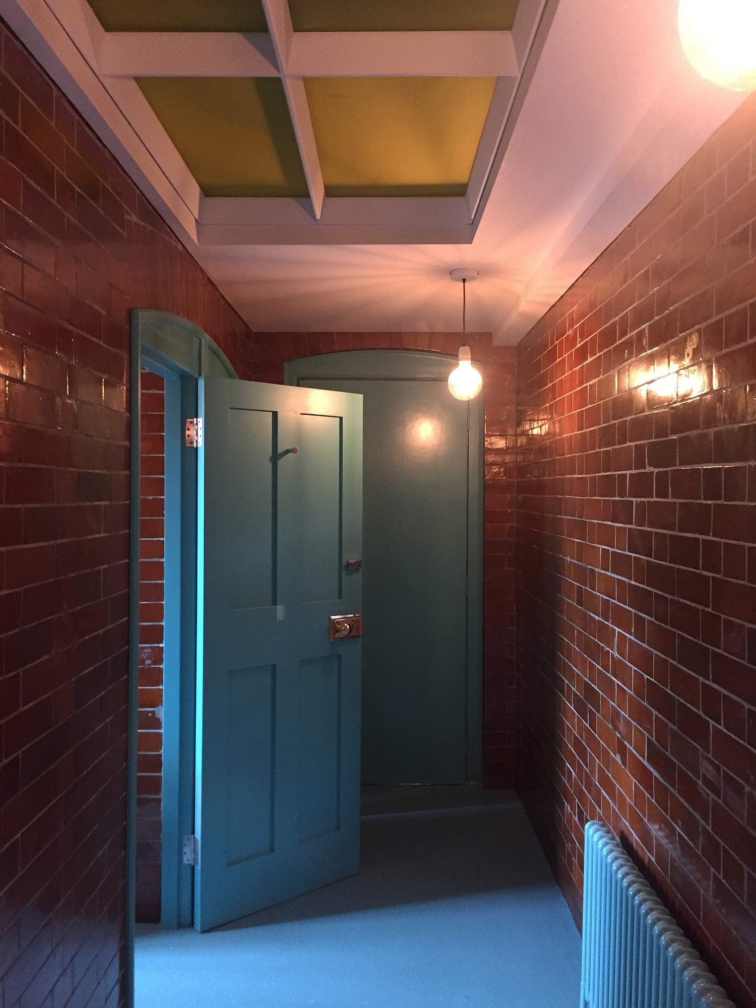Refurbished lavatories: the original tiles have been restored and a turquoise blue paint and floor chosen to create a contrast in colour and texture that reveals their quality.