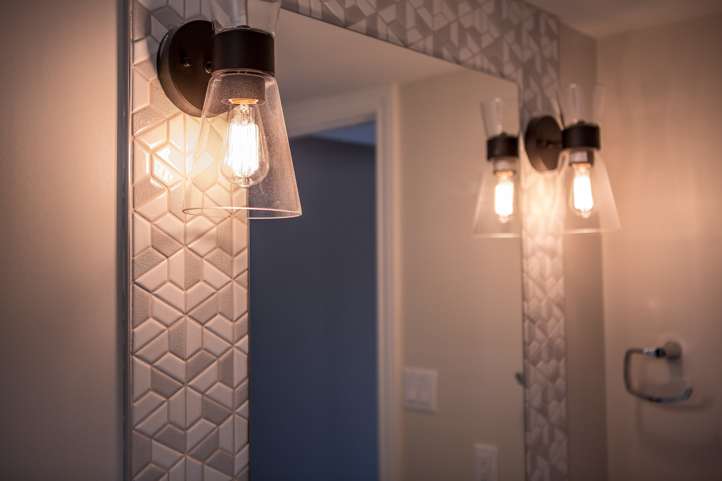 Sconces at eye-level. The tiles also create contrast.