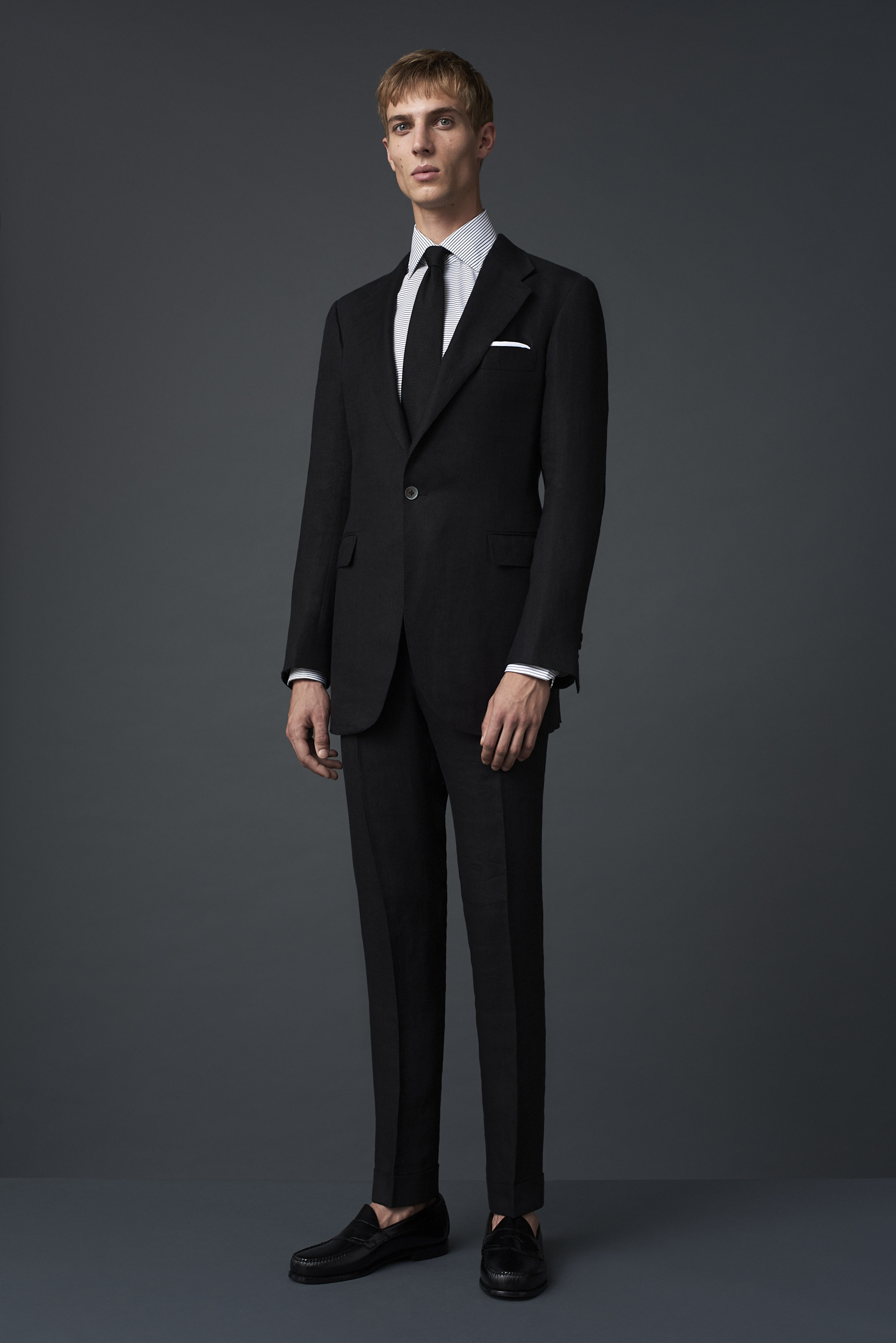 Black Irish twill linen suit with a one button notch lapel. Worn with a horizontal striped Egyptian cotton shirt and a black grenadine silk tie, made in Como.