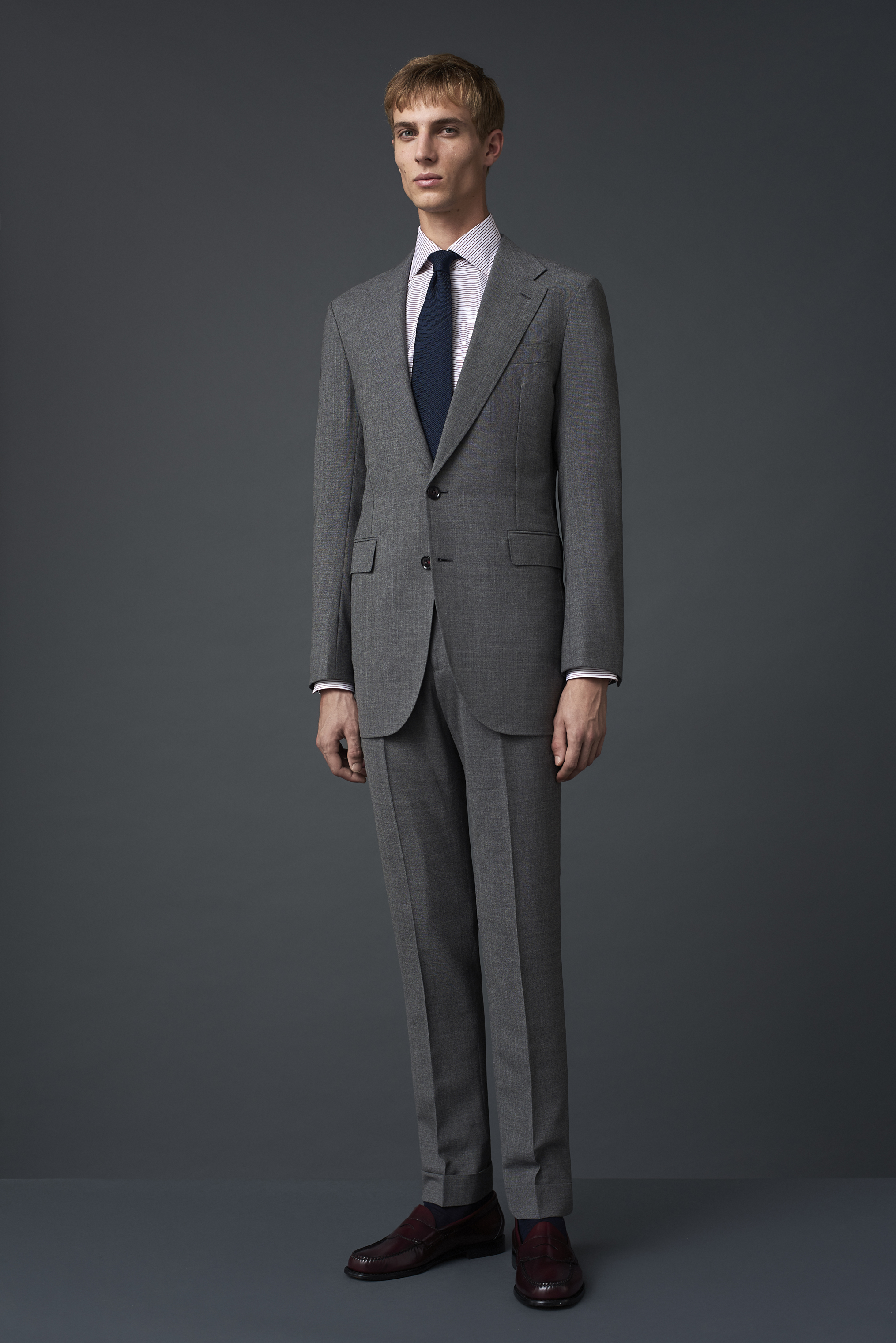 Mid grey fresco three ply suit with a wide notch lapel, woven in Huddersfield. Worn with a horizontal burgundy striped shirt and a French navy grenadine tie made in Como, Italy.