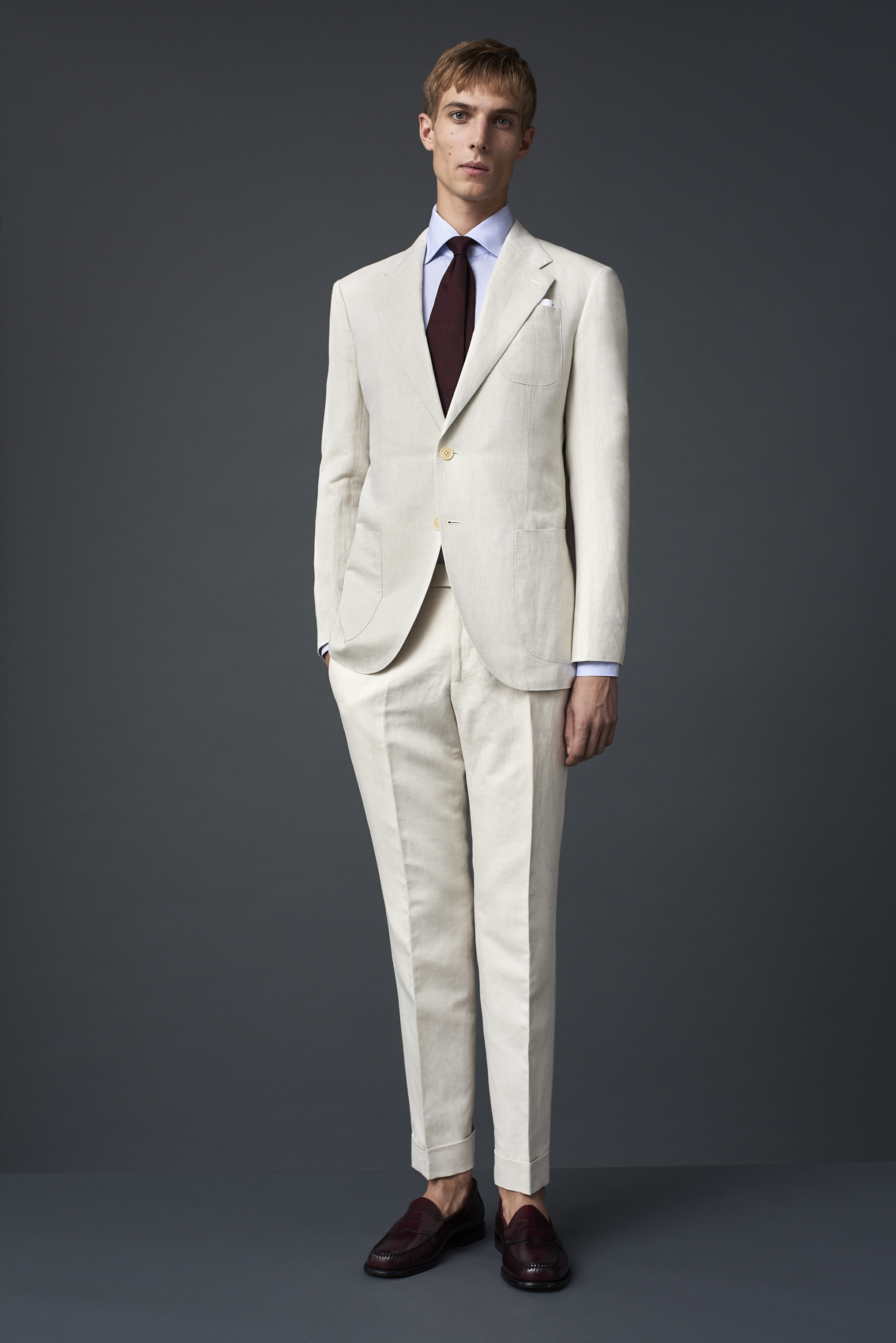 Ivory cotton linen suit woven in Como, with three patch pockets. Worn with an ice blue Egyptian cotton twill shirt and a burgundy grenadine tie.