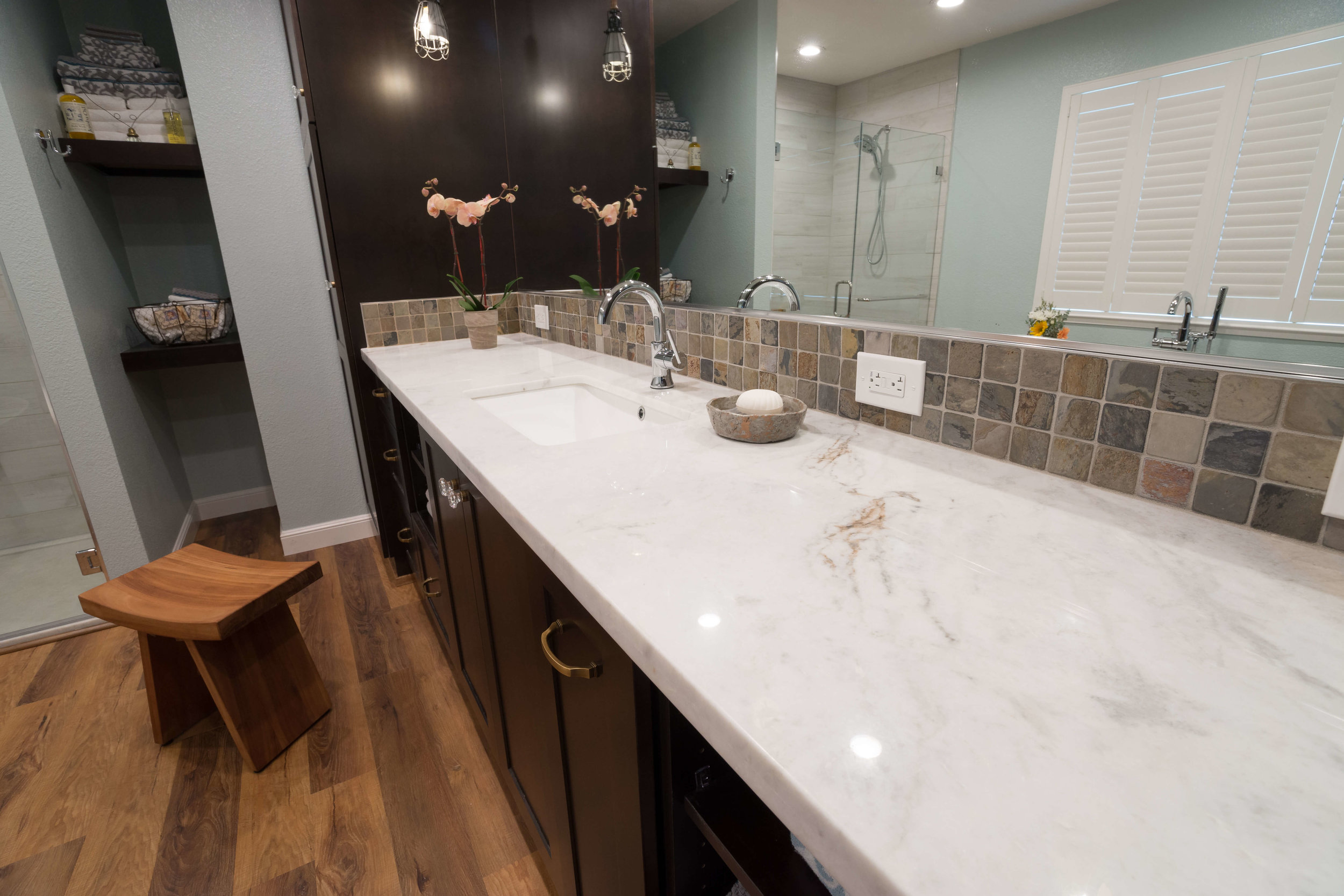 Undermount sink, marble counter, expansive dark wood cabinets and rustic backsplash combine warmth, practicality and elegance.