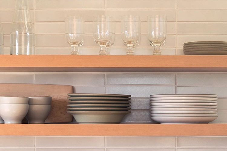 Heath Ceramics handmade dinner service and tile backsplash on open shelving.