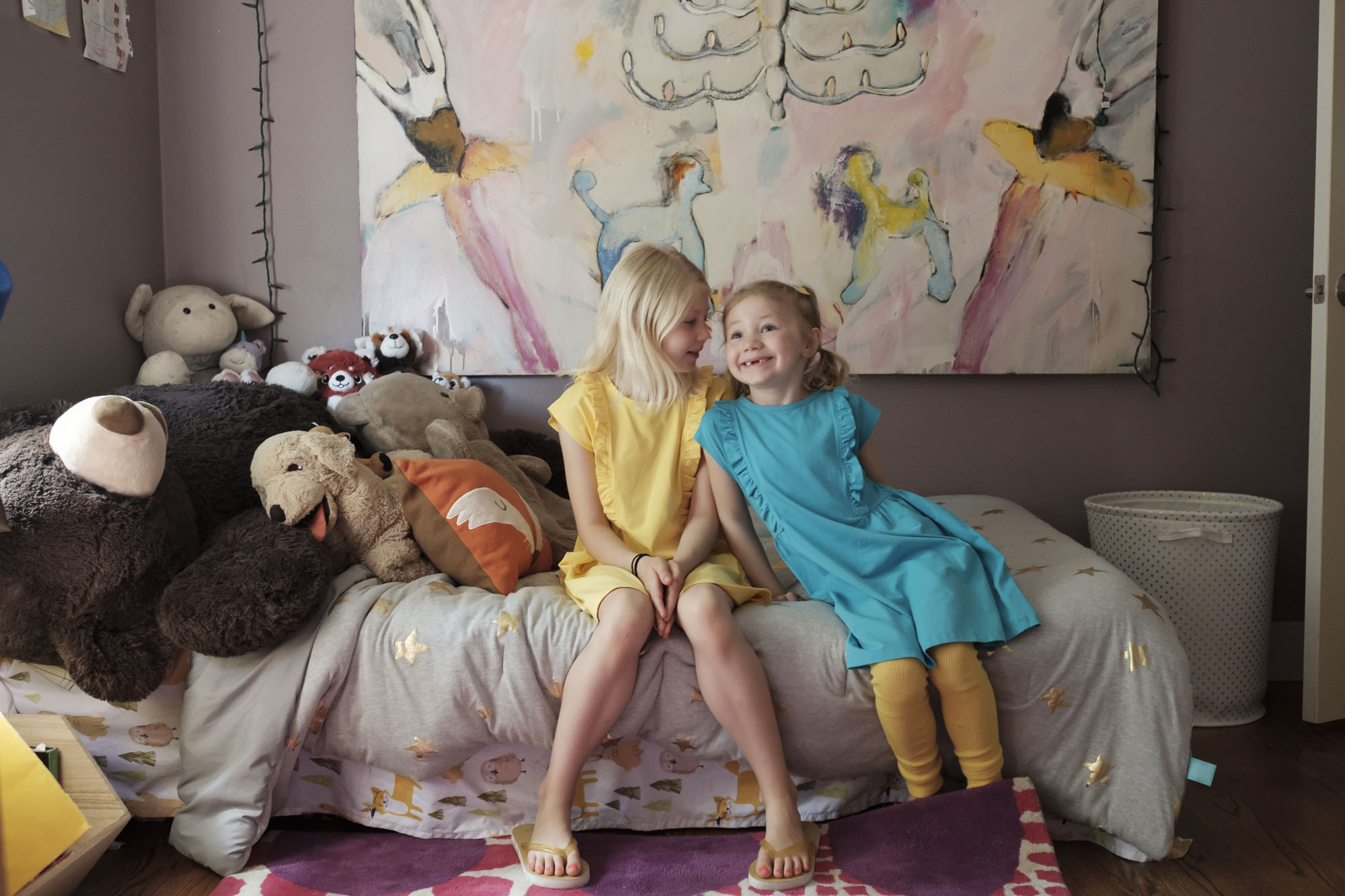 two girls in colorful dresses sitting on a bed