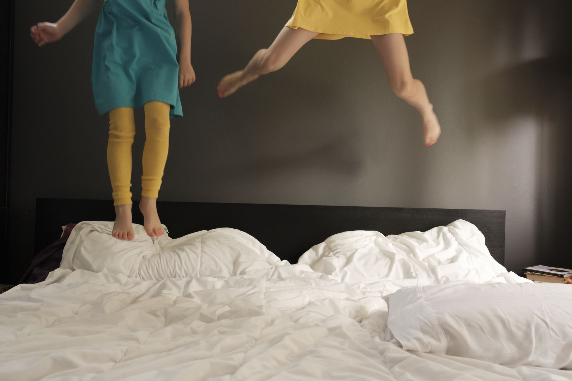 two girls in colorful dresses jumping on a bed