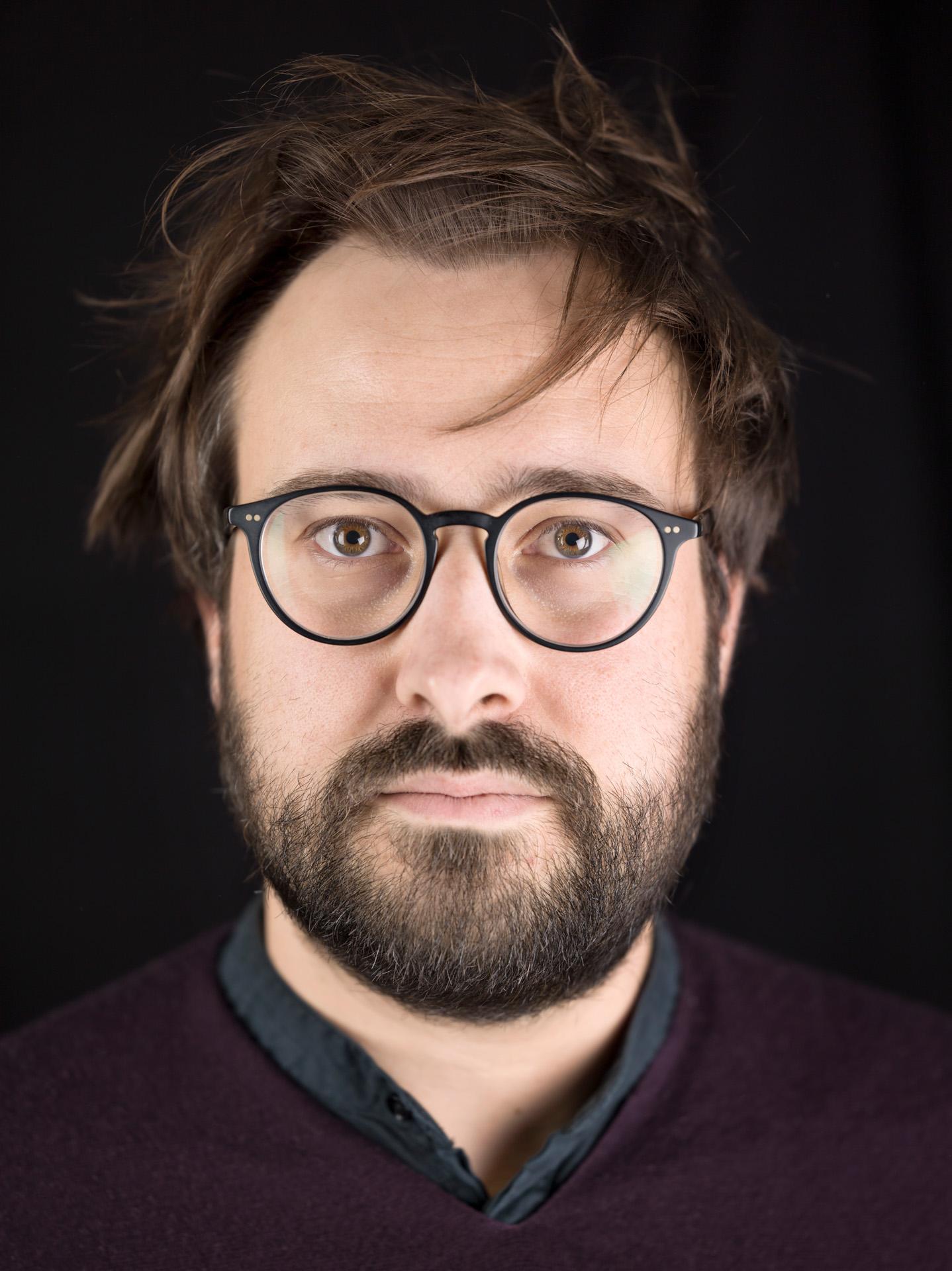 Porträtfotografie: Fotograf Caspar Sessler vor schwarzem Hintergrund