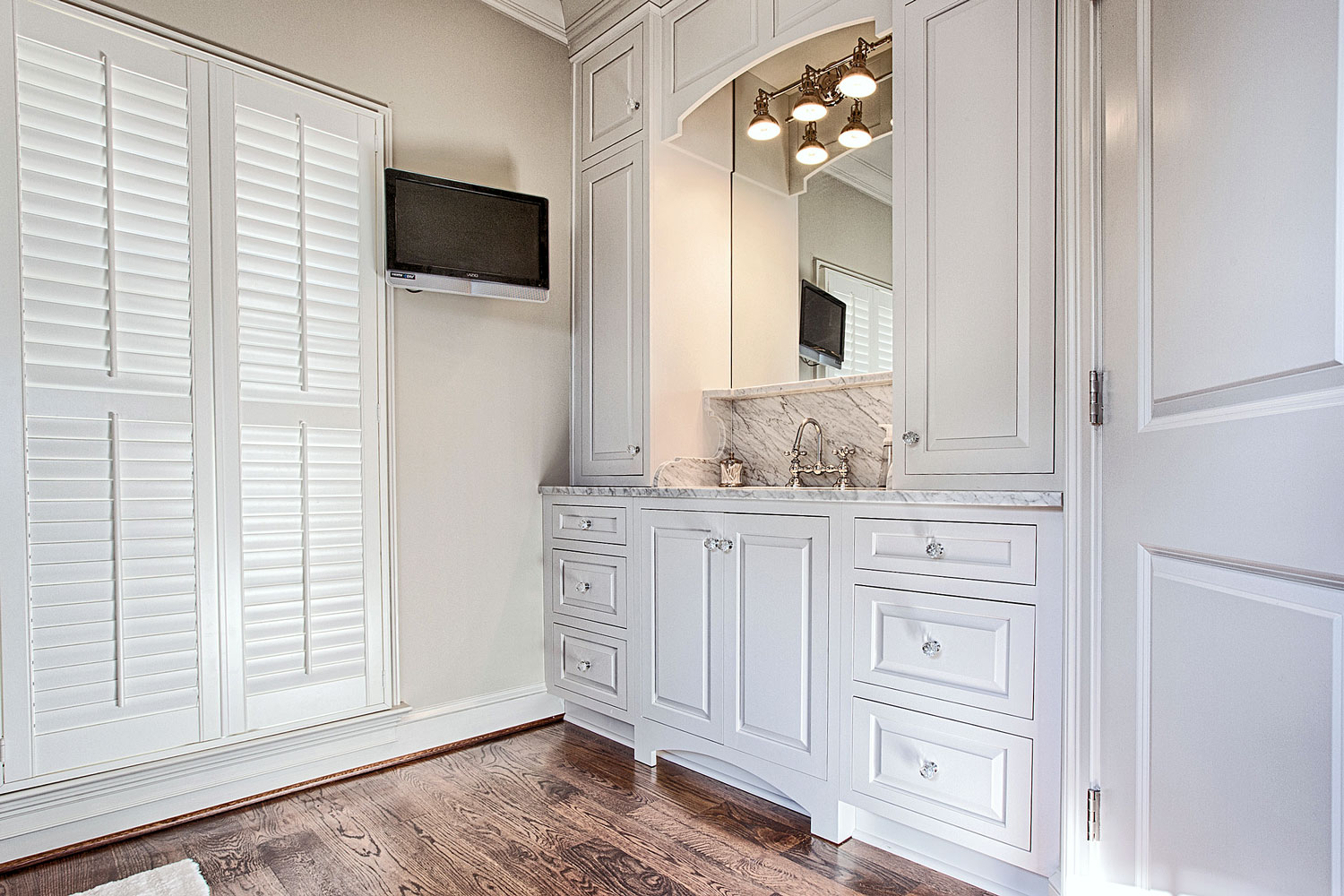 A Wall Mounted Television Located In A Traditional Bathroom Design