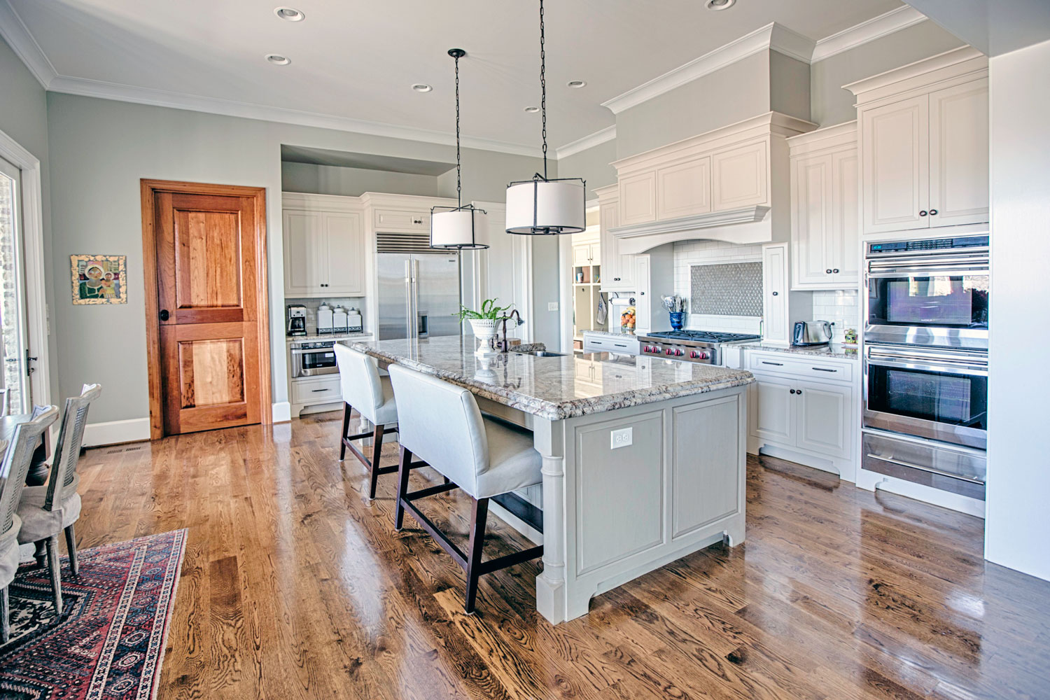The kitchen island contains a stainless steel farmers sink.