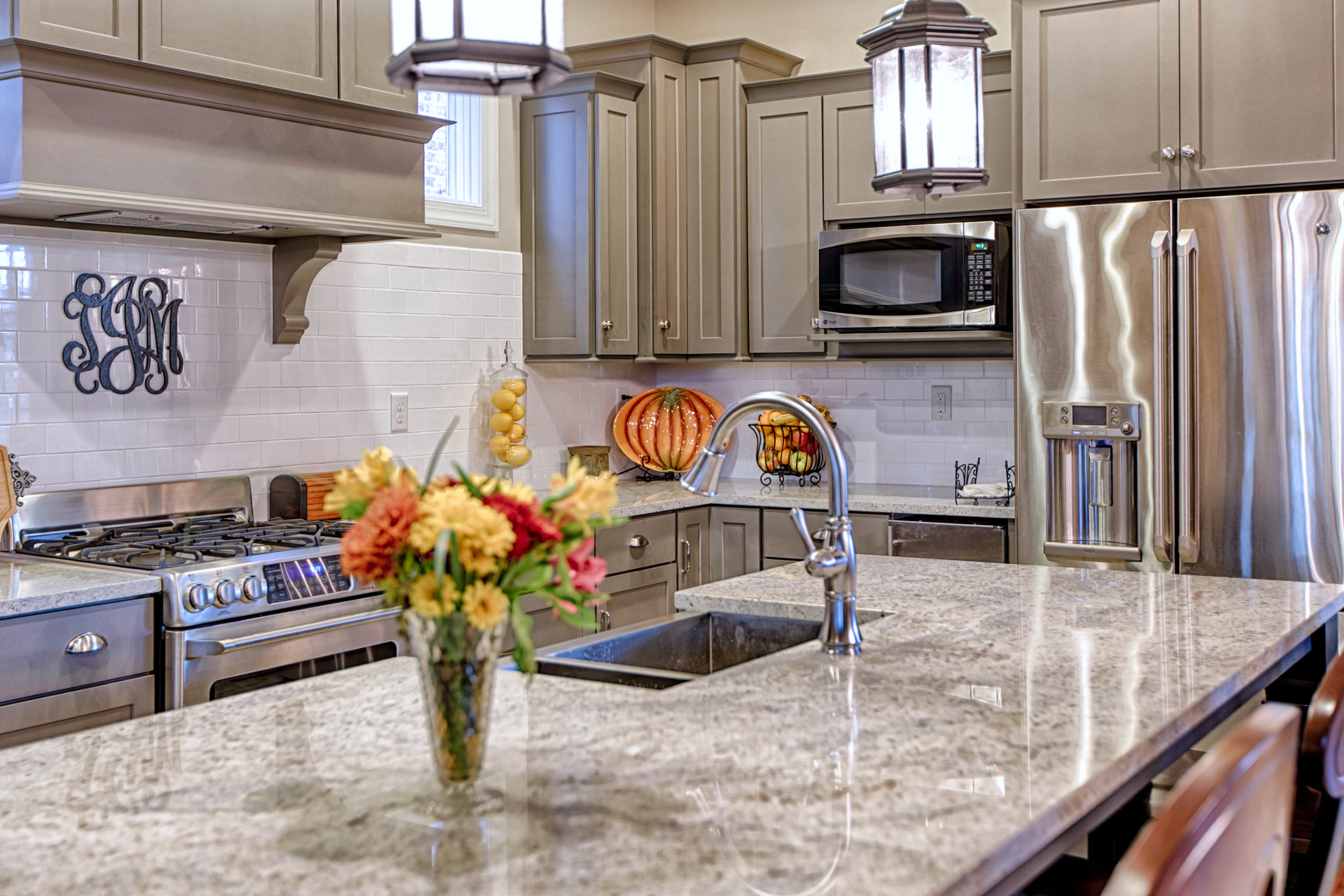 The apron front farmhouse sink sits within the granite countertop island.