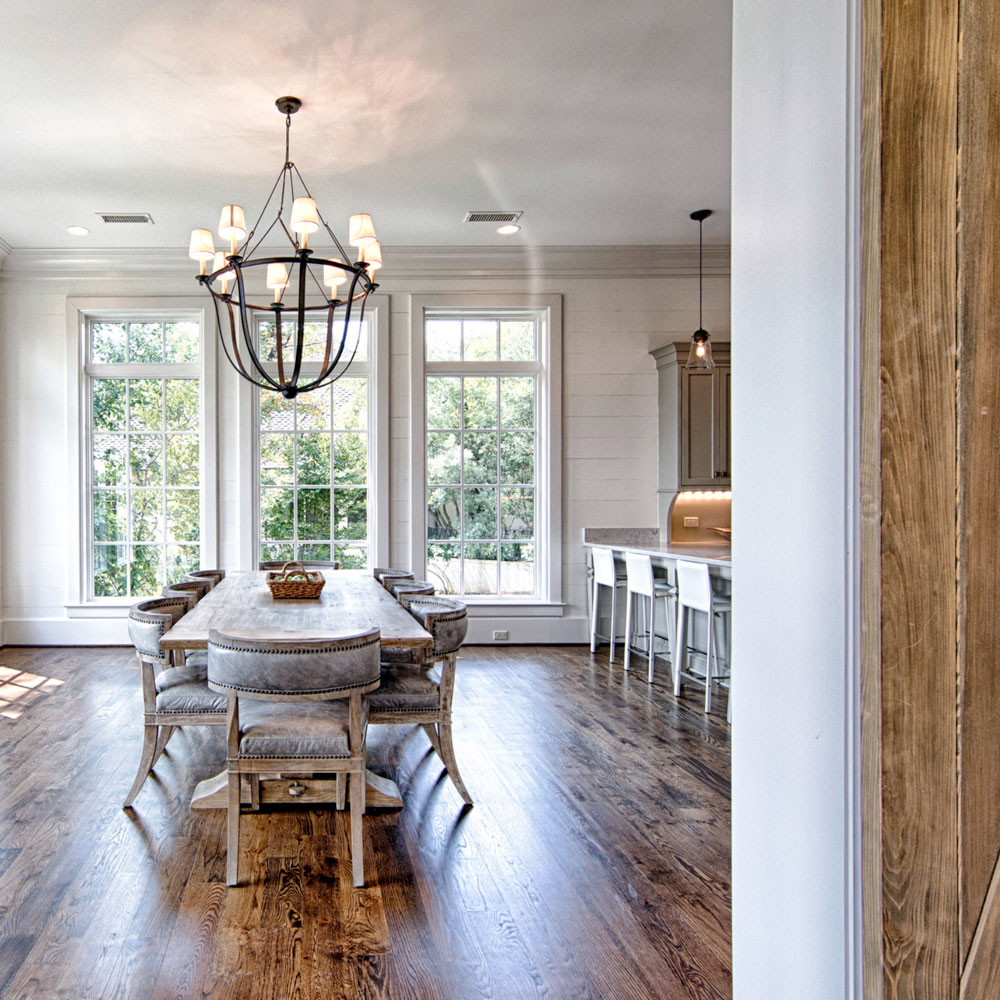 Dark stained wood flooring, beams, and barn doors contribute to the rustic look.