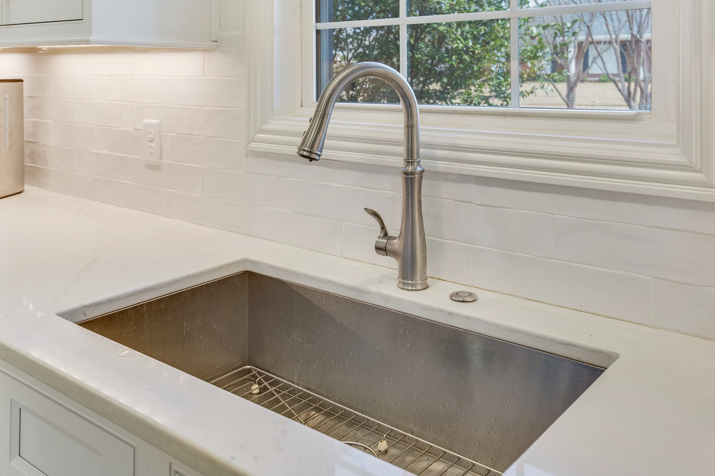 Single bowl Kohler Vault undermount stainless steel sink with push button for garbage disposal.