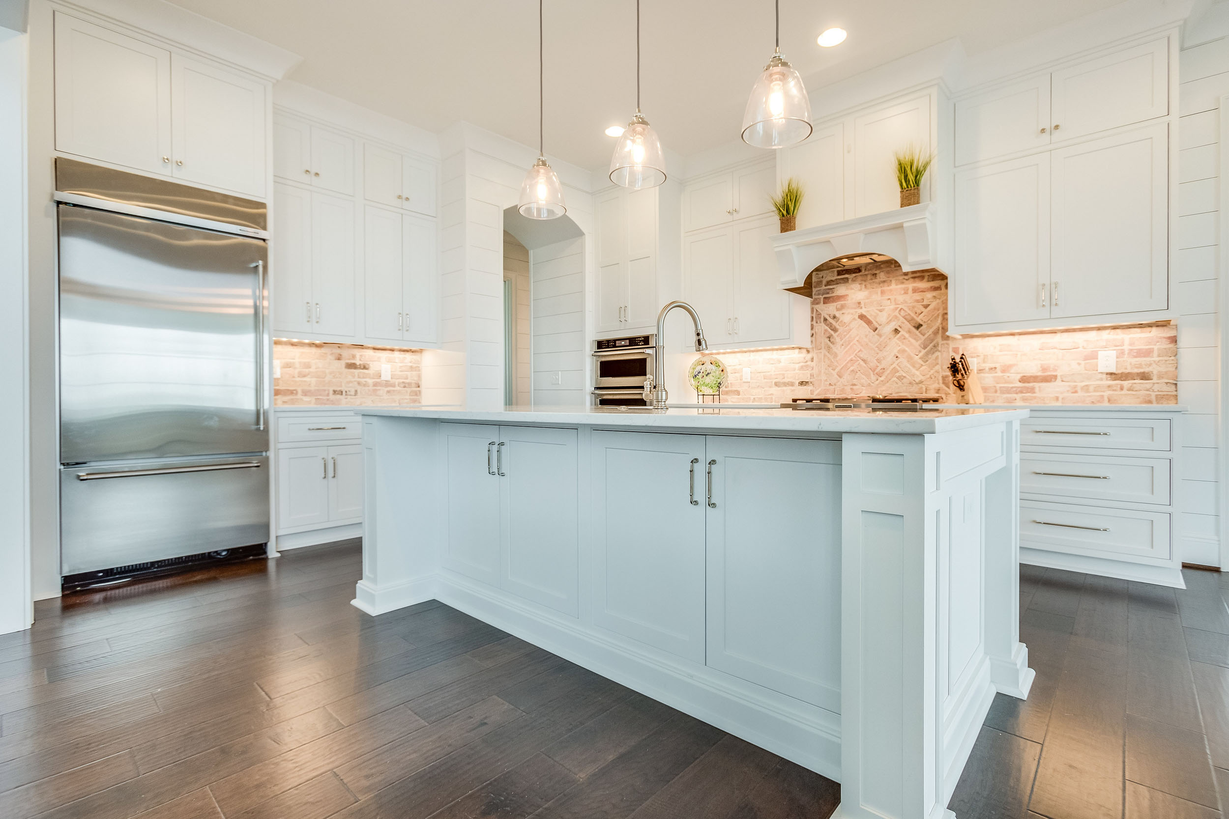 A kitchen island with a Kohler Whitehaven apron front sink.