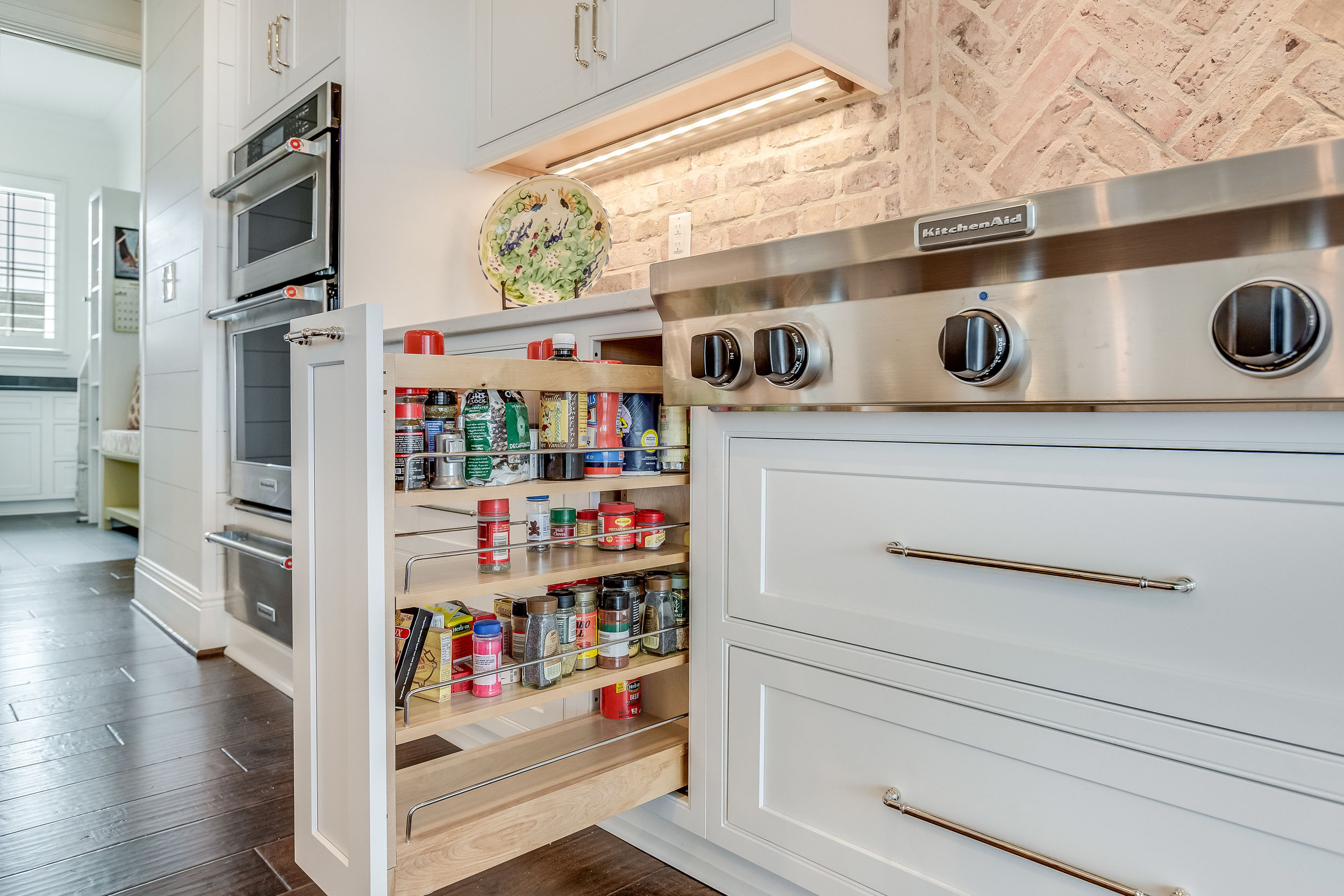 Cabinet pull out spice drawer with adjustable height storage.
