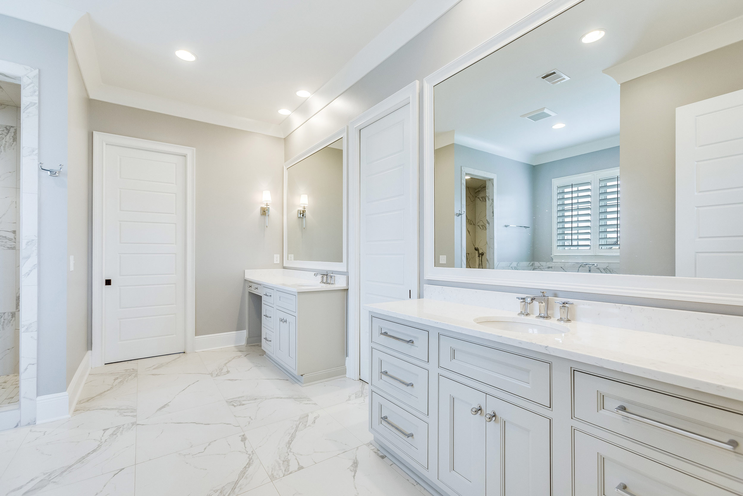 This elegant white bathroom was designed to have two vanities, a walk-in shower, and a freestanding tub.