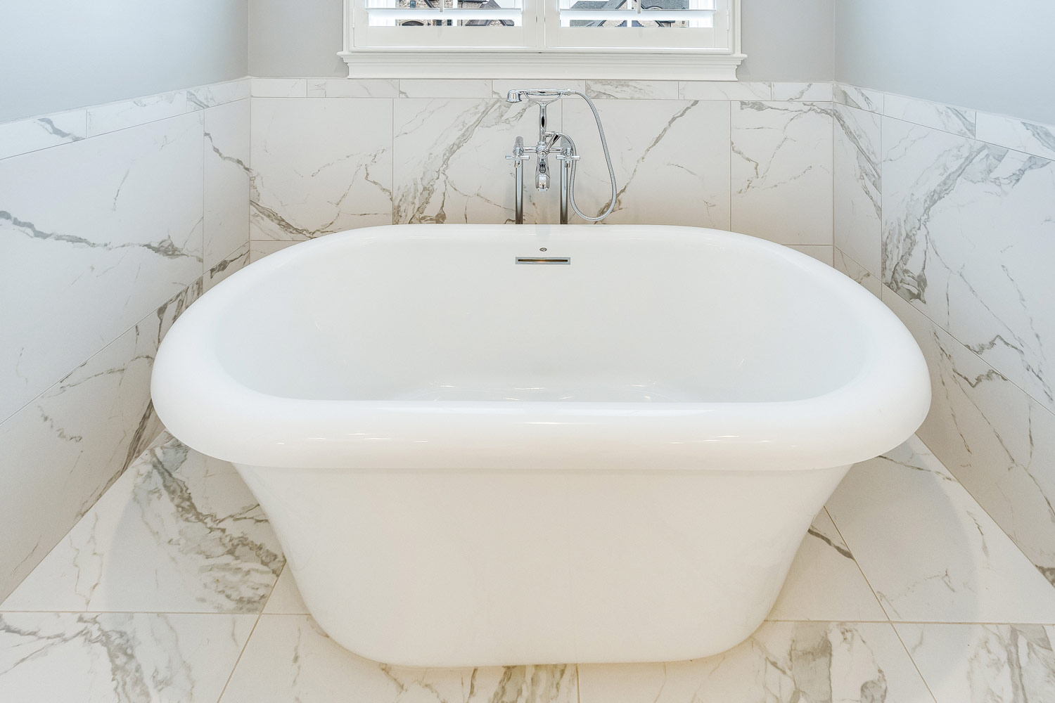 The master suite has a freestanding tub with polished chrome tub filler