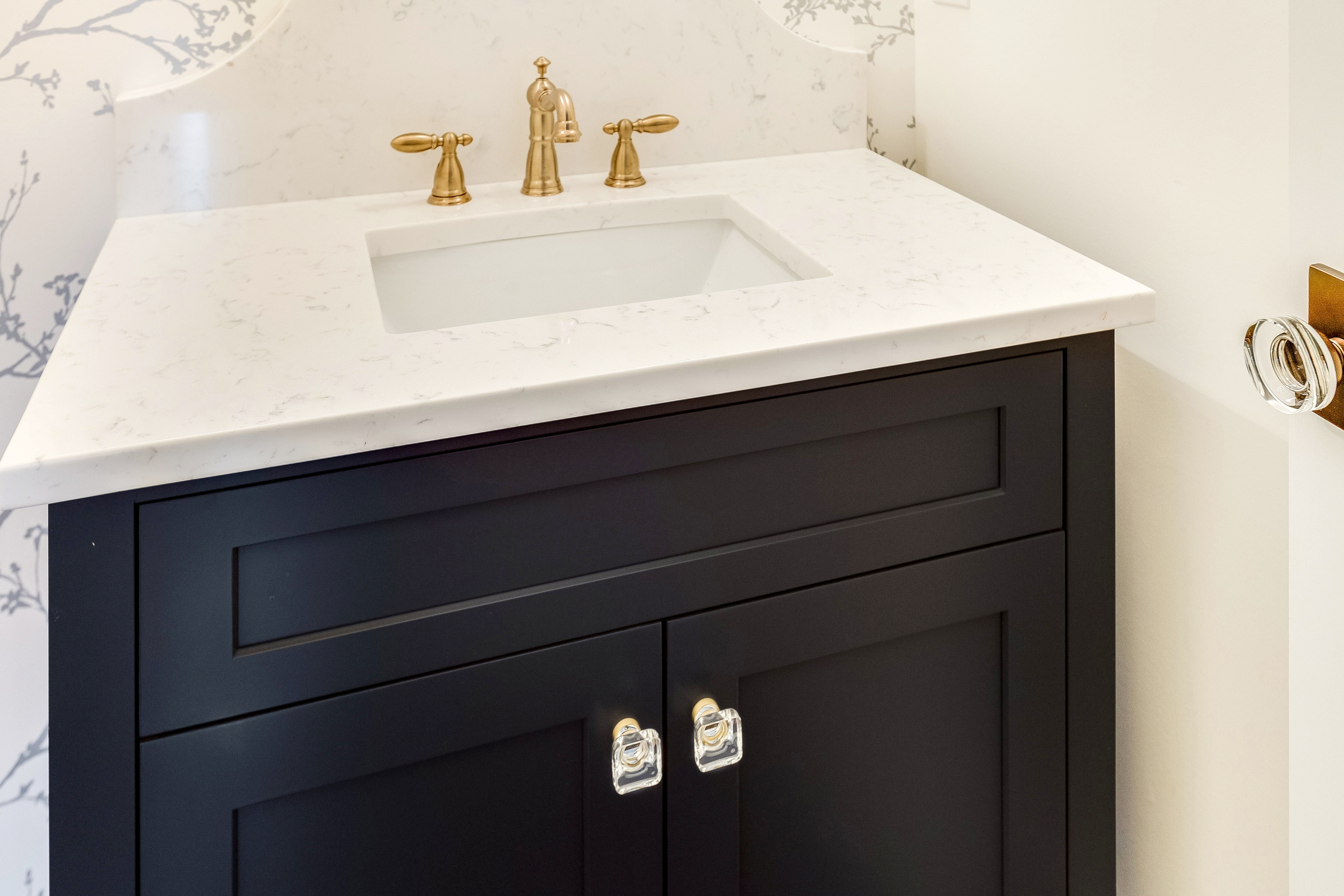 The cabinet is in a Hale Navy color by Shiloh Cabinetry and the cabinet hardware is Intek Crystal knobs.