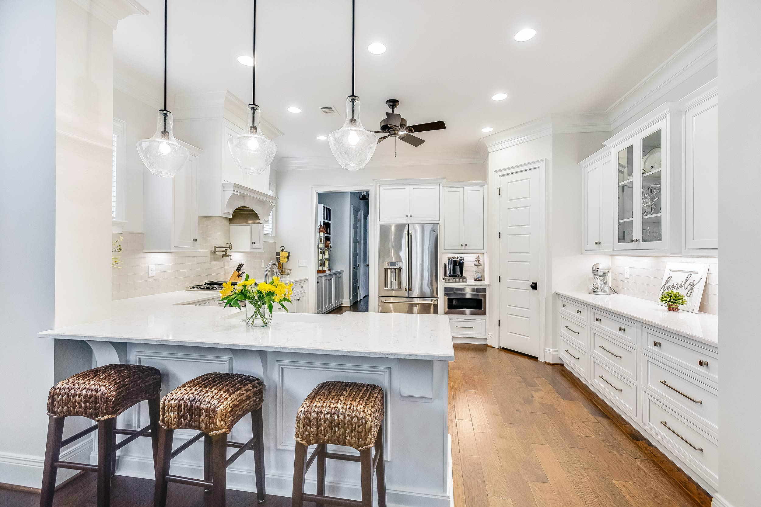 A new construction kitchen design with oversized kitchen Island corbels, seeded glass pendant lighting, an engineered wood floor, and a Sharp microwave drawer.