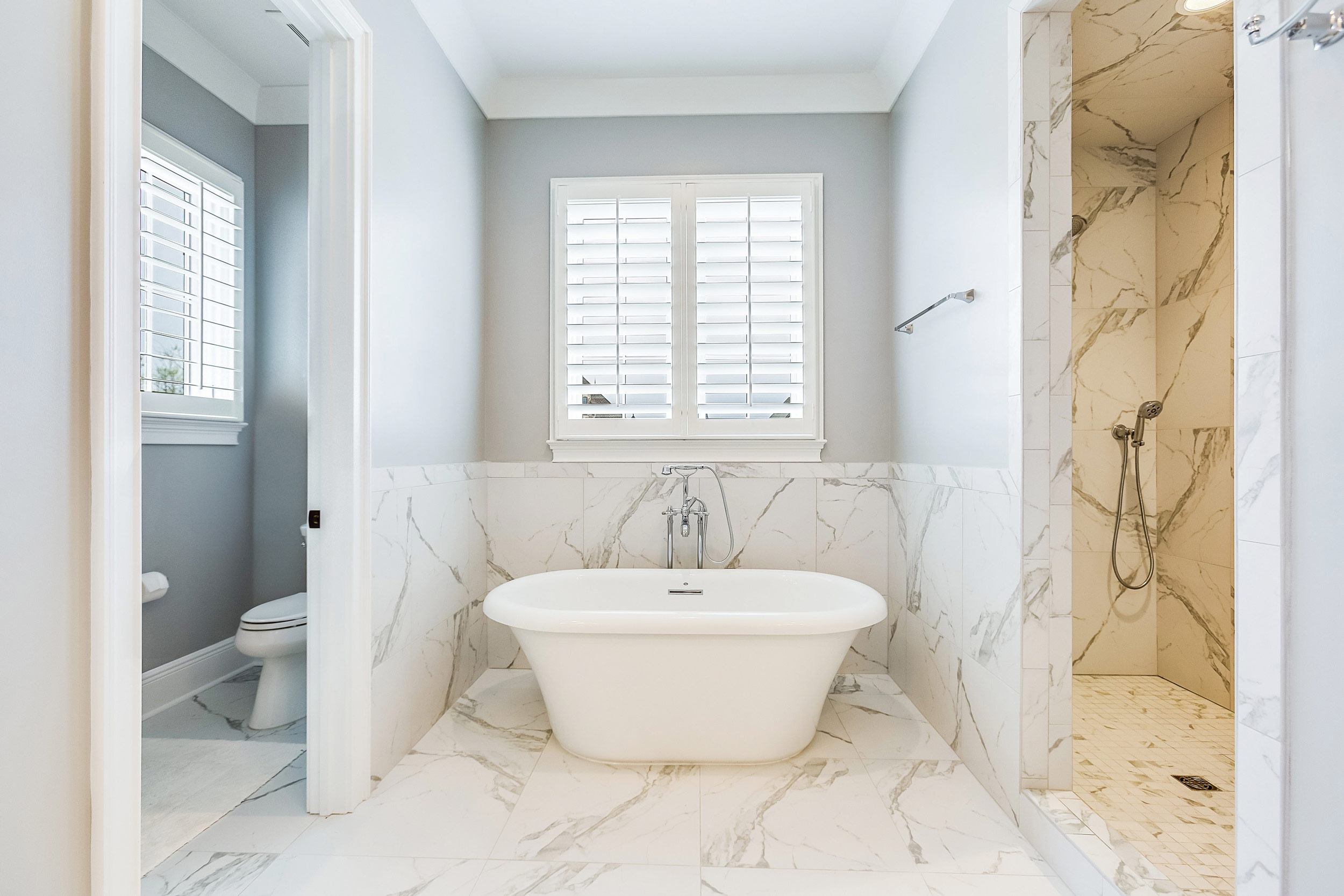 This classic bath is created with custom beaded inset gray cabinets, a Carrera marble cabinet top.