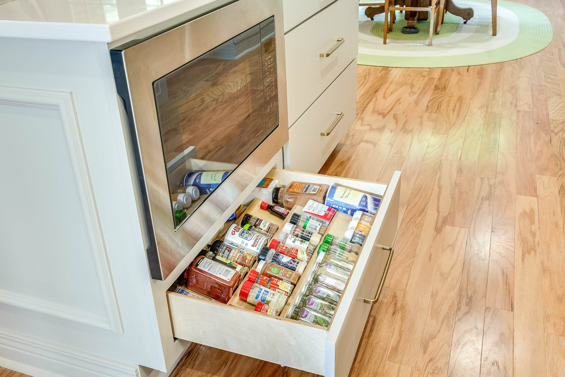 A spice drawer was placed below the built-in microwave in the kitchen island.