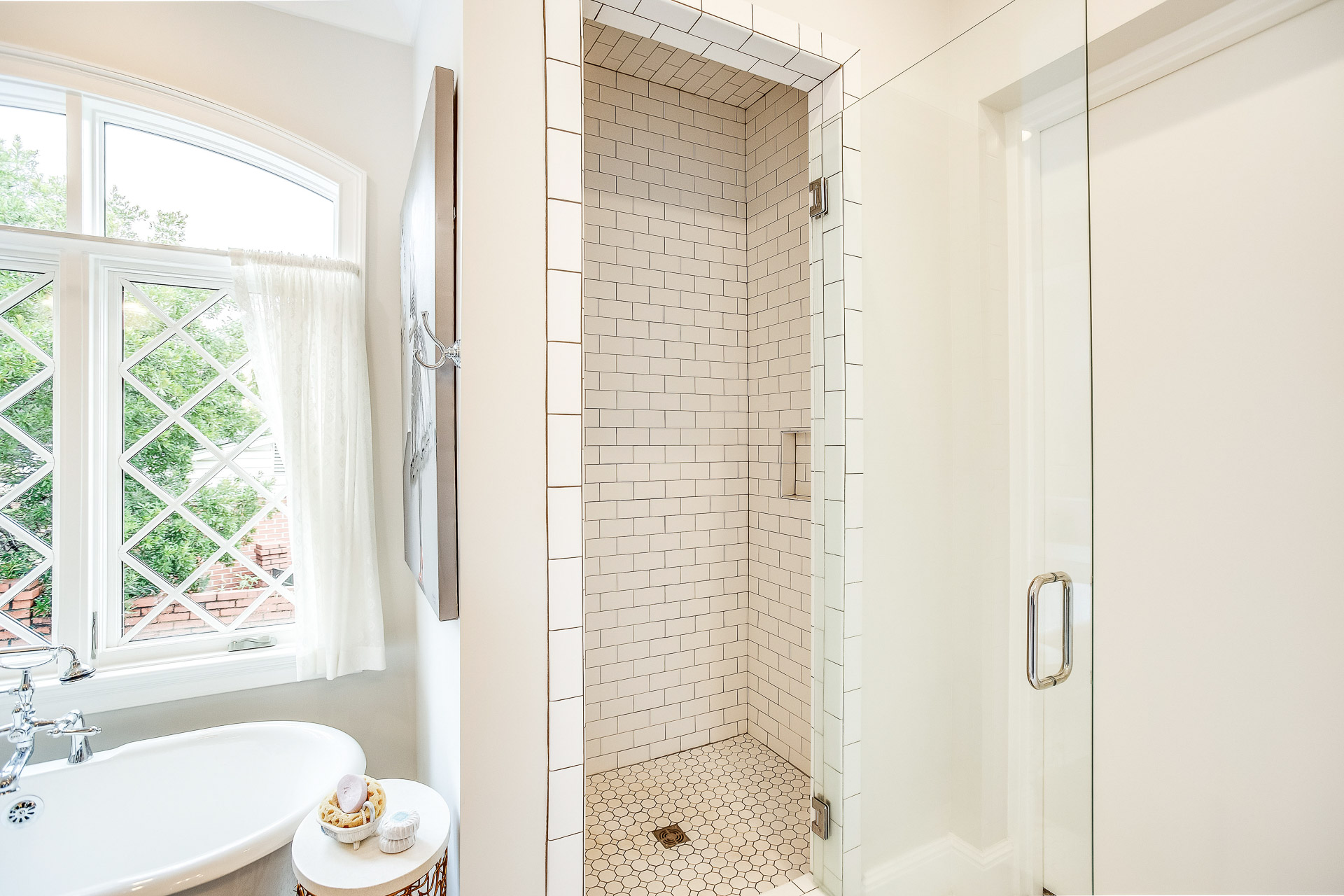 A separate walk-in shower with glass door and chrome hardware.