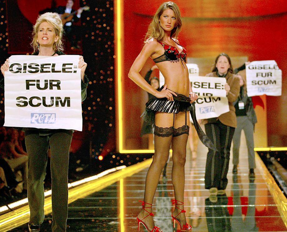Manifestantes de PETA suben al escenario mientras Gisele Bundchen posa durante el desfile de modas de Victoria´s Secret en 2002. Foto: Getty Images