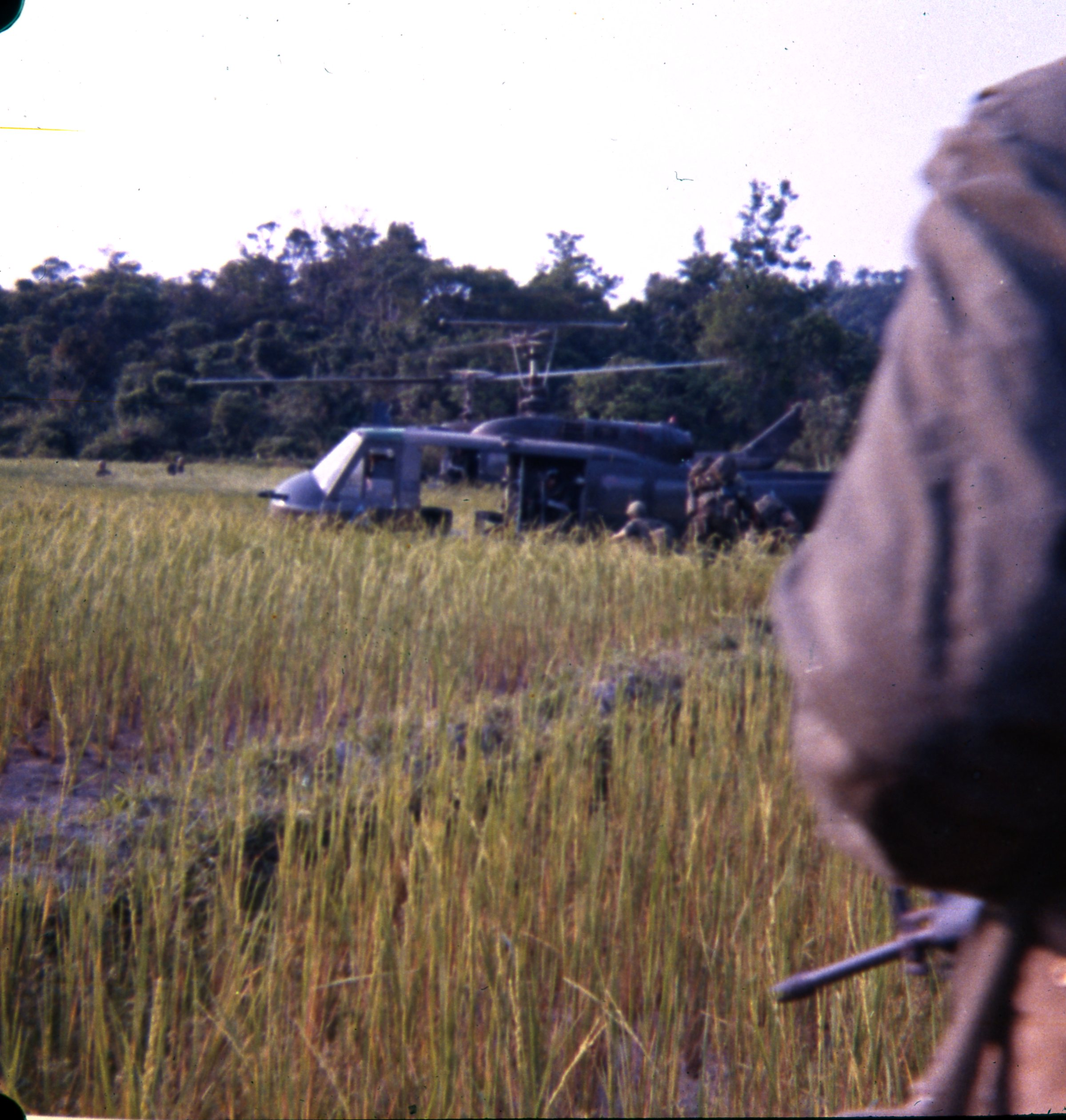 Alpha Company soldiers make their way toward choppers waiting in a rice paddy landing zone.