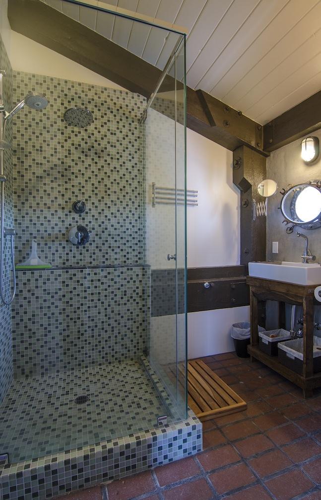 Master bath with tiled shower and porthole window.