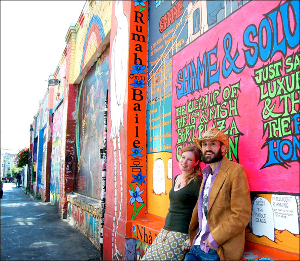 Megan Wilson and Christopher Statton in front of  Shame & Solutions  mural