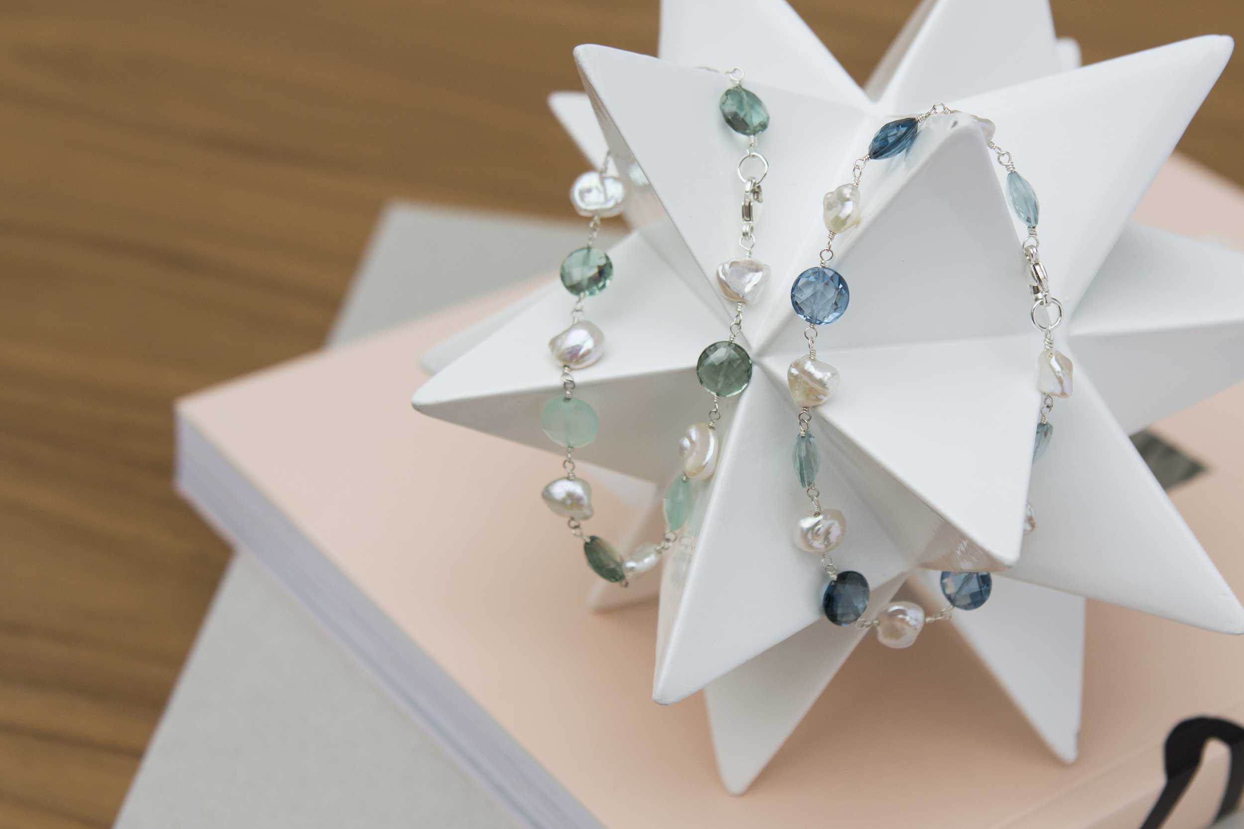 Two semi-precious and pearl bracelets displayed on a white star shape.