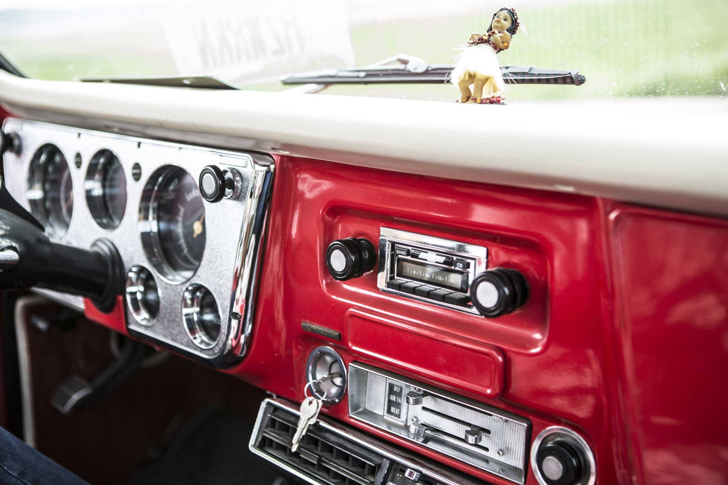 Red dashboard of old pickup truck with Hula girl.