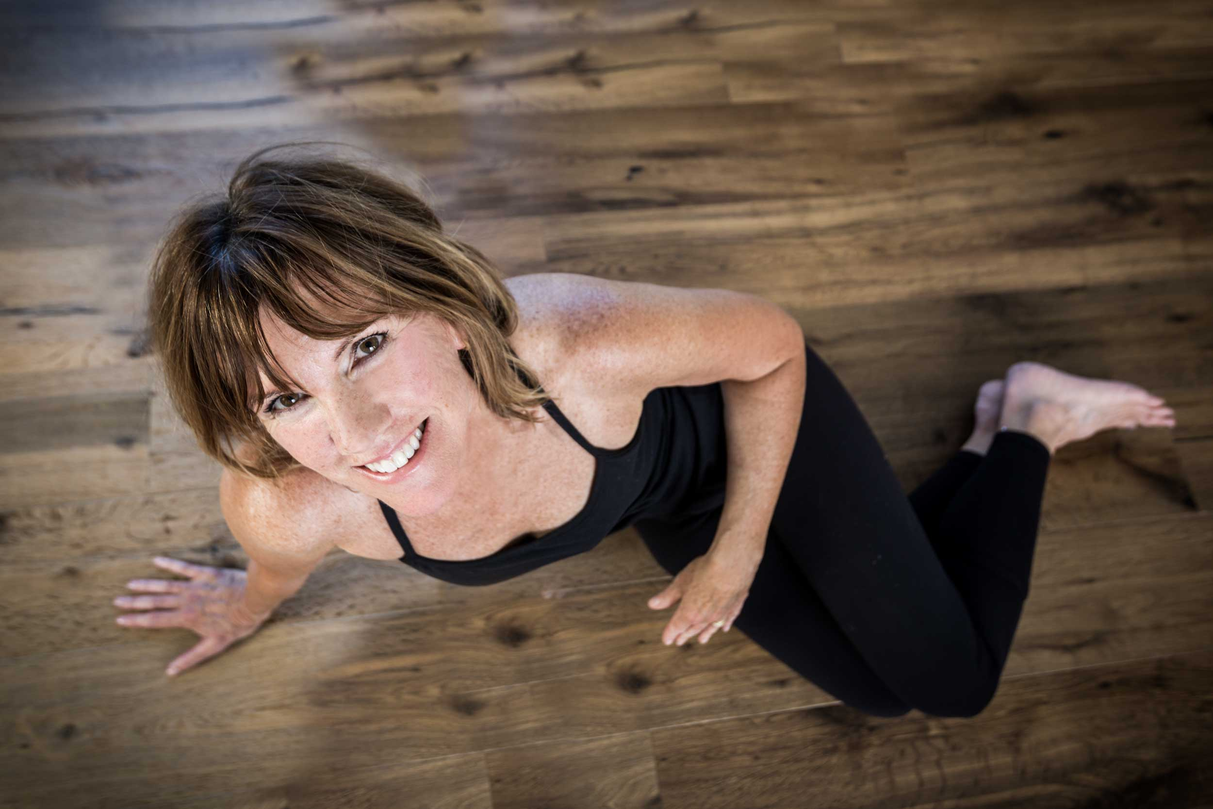 Top down shot of Pilates instructor, Pam Howard on wood floor.