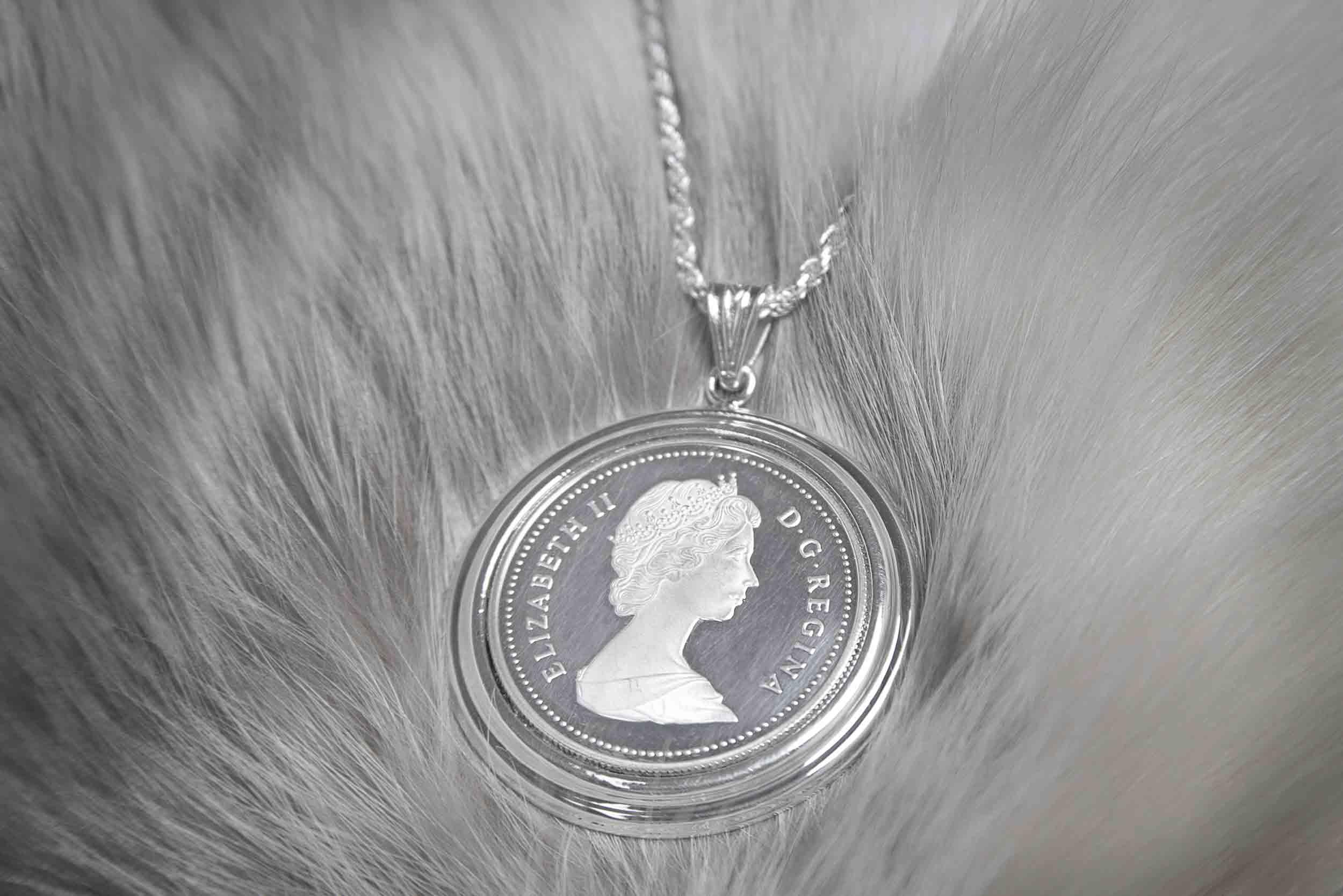 The Queen Elizabeth silver dollar pendant on a fur background.