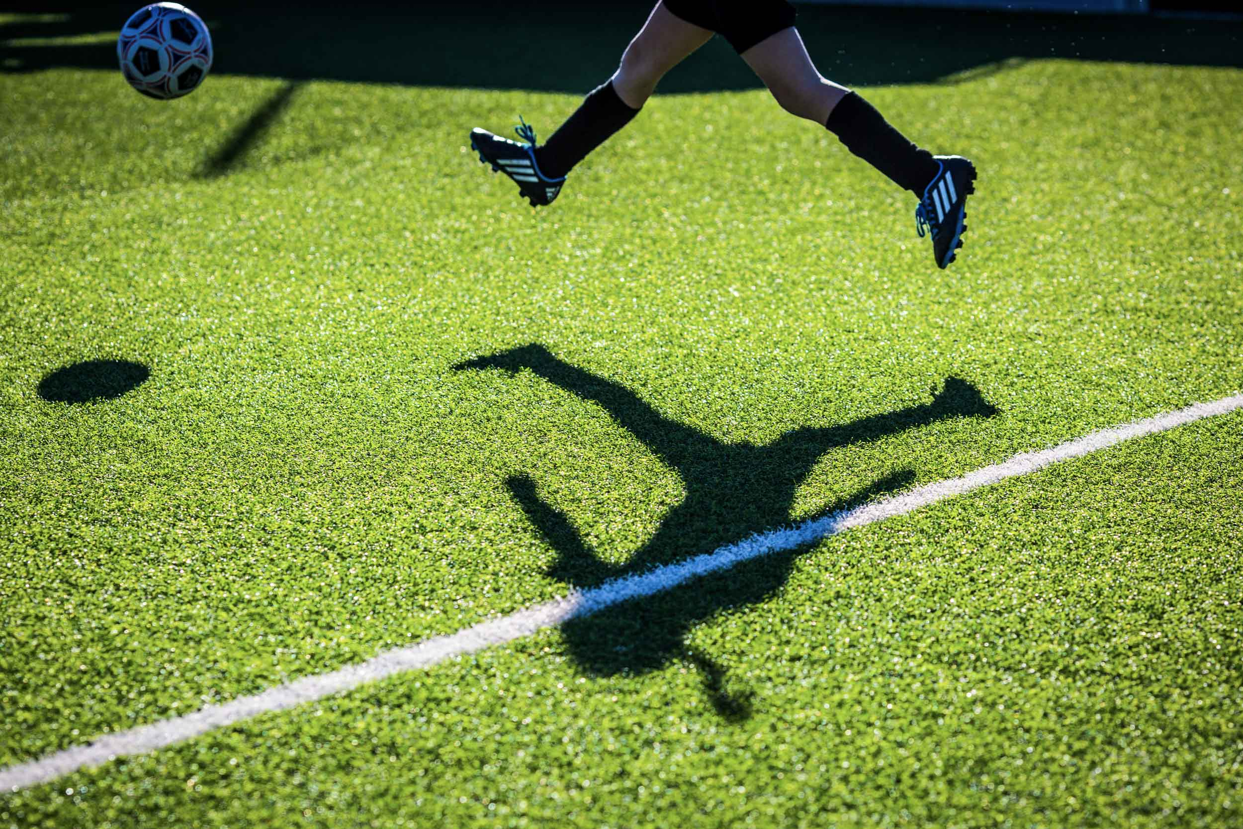 Kid feet jumping in the air with shadow on turf.