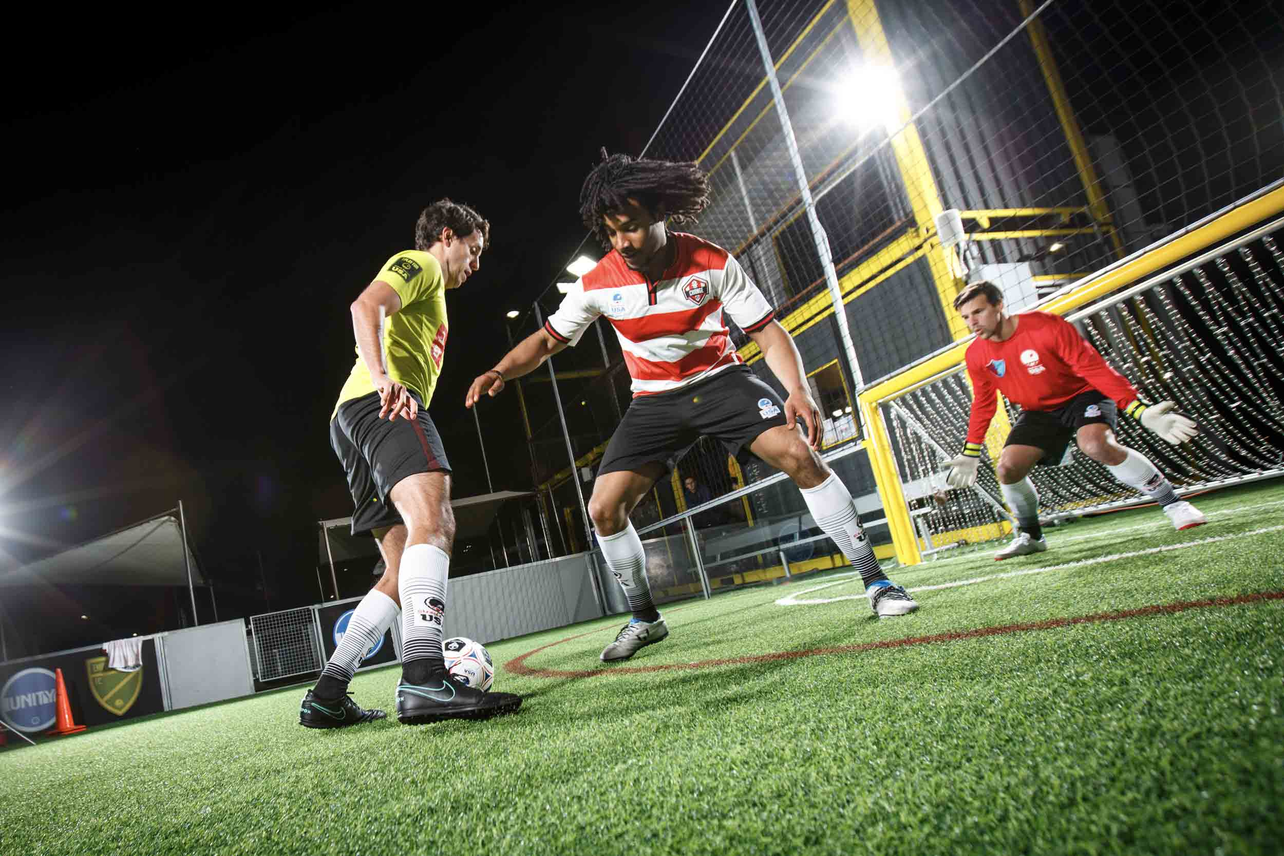 Three men playing small-sided soccer at Urban Soccer Park in San Francisco at night.