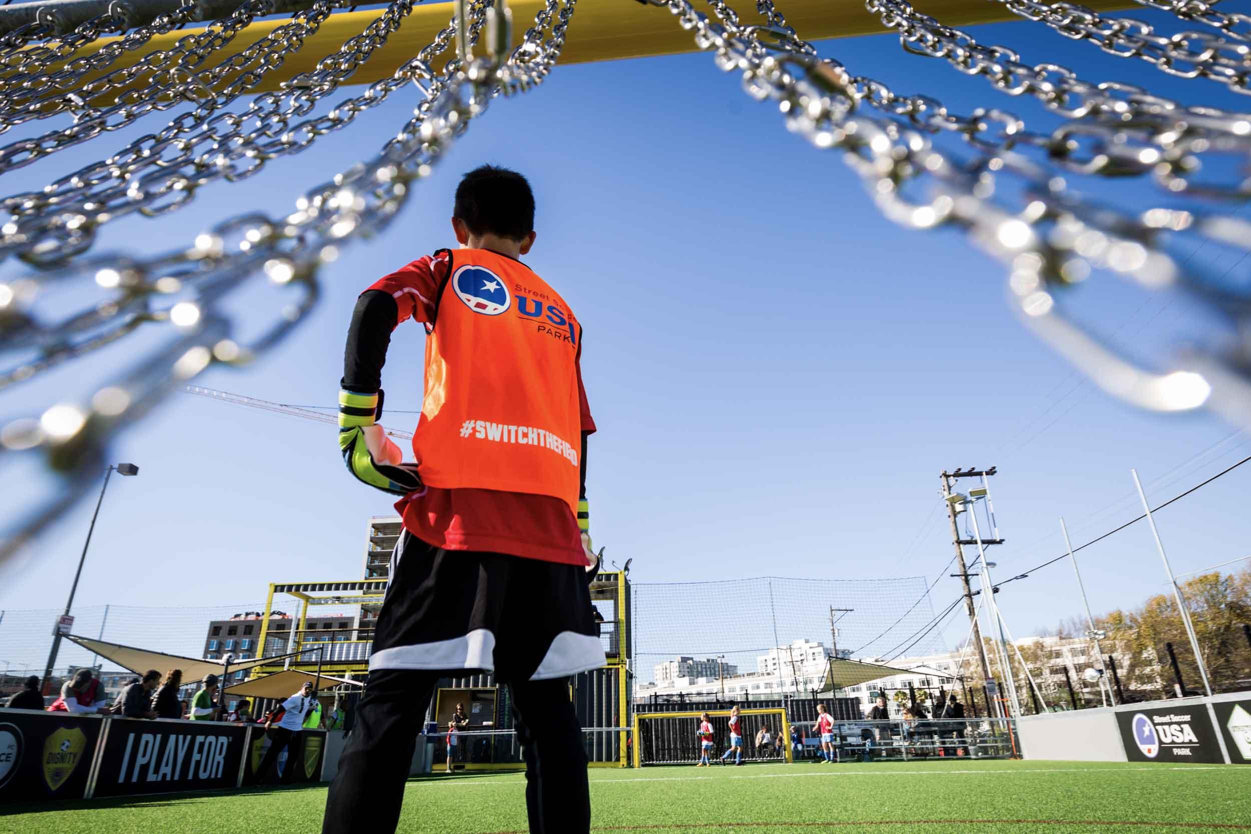 Back view of kid goalie on soccer field in San Francisco.