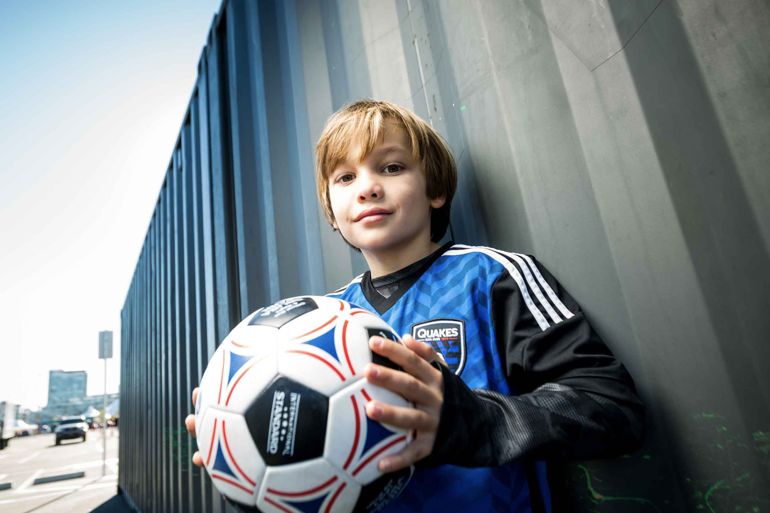 A young boy soccer player holding a ball in front of a shipping container at Urban Soccer Park.