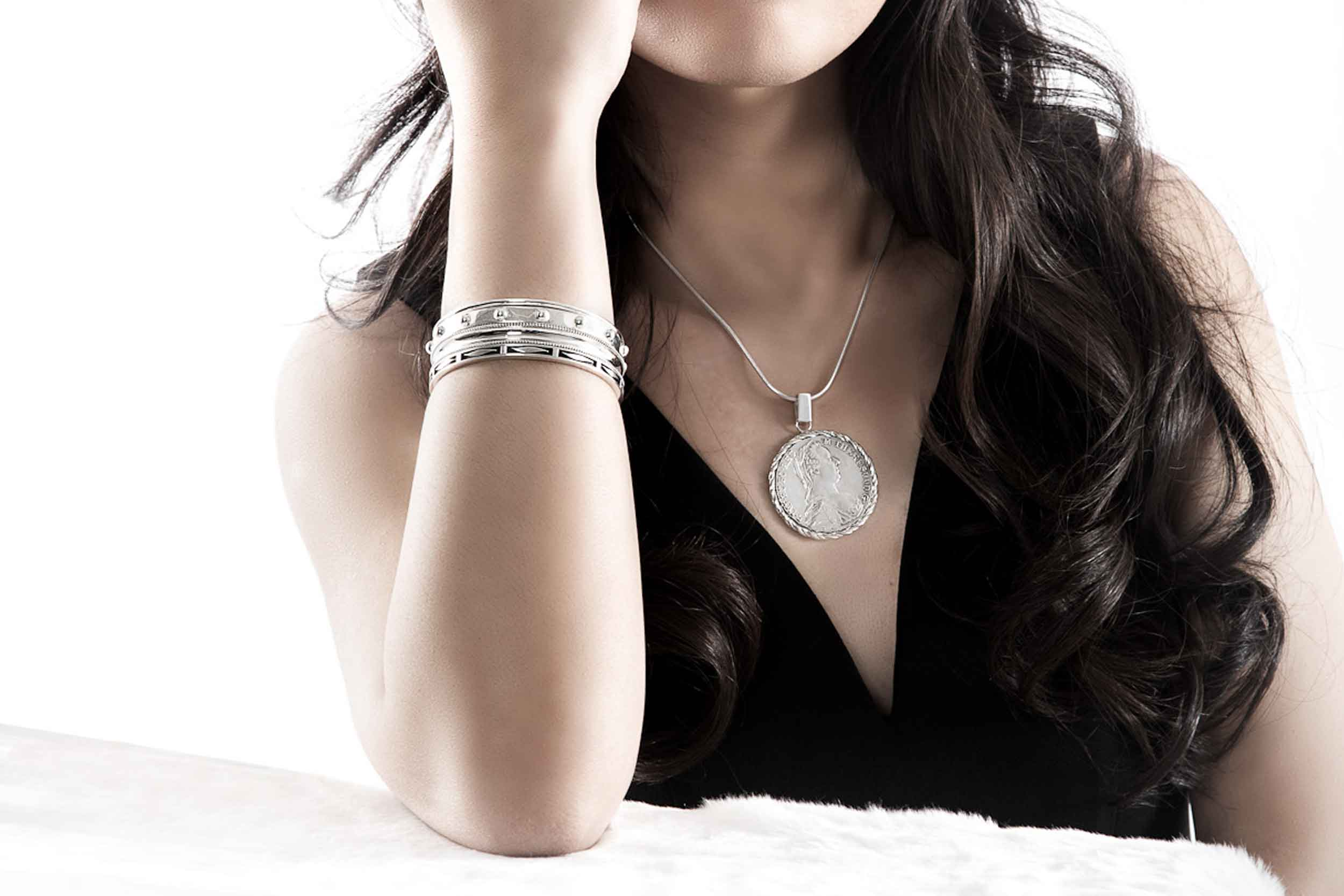 Model showing Thomas Pinck bangles and the Maria Theresa braided silver dollar pendant.