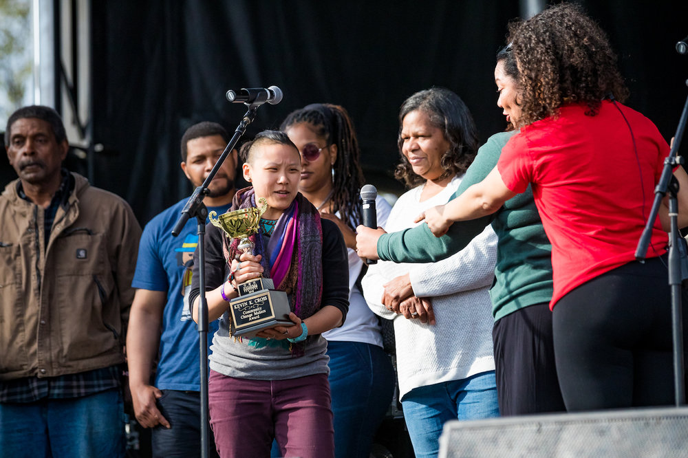 Minna Nilanot, surrounded by Kevin's family and friends, accepts the inaugural Kevin Kareem Cross Change Makers Award at the 2018 National Cannabis Festival on April 21, 2018