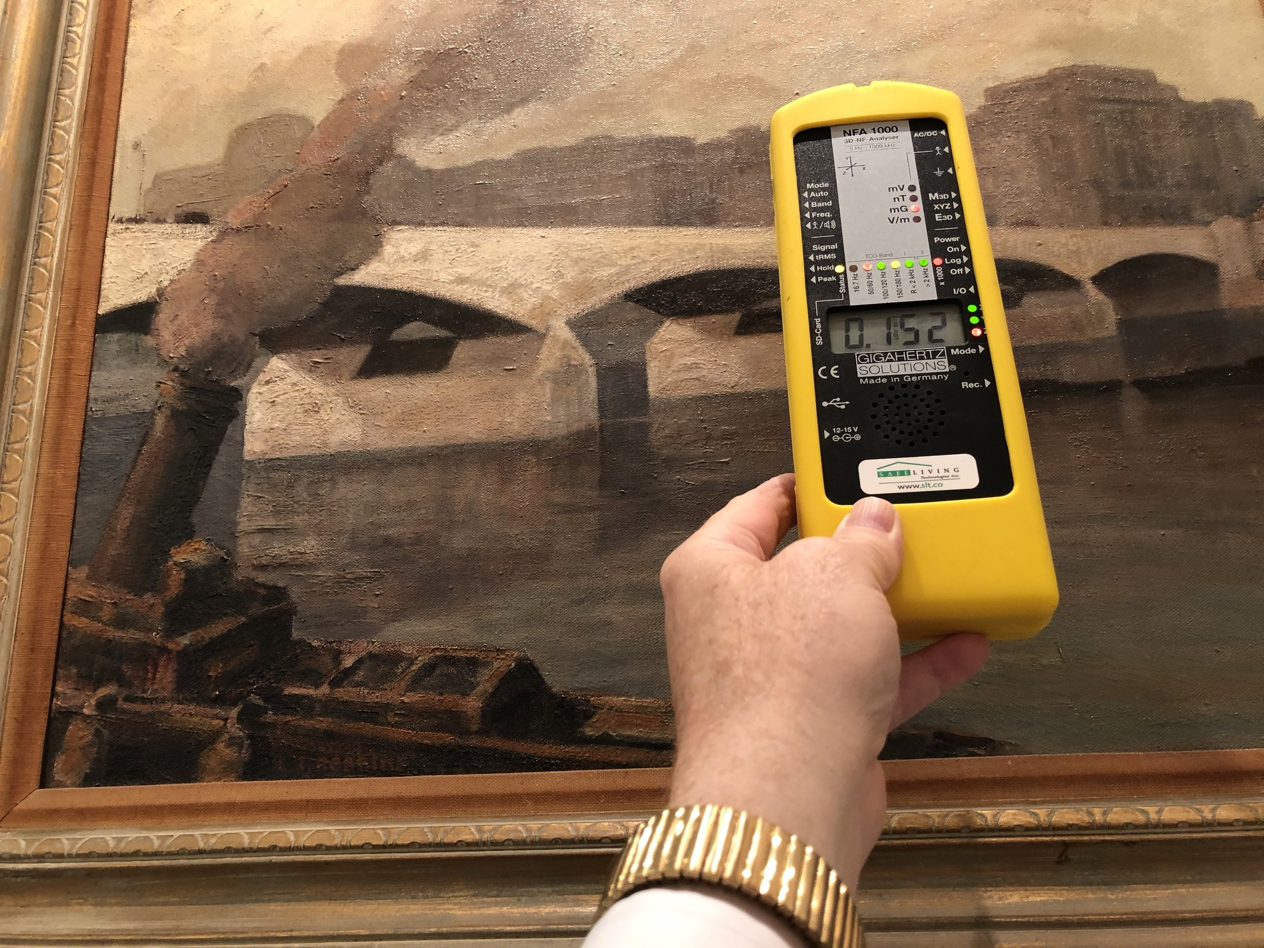 Using a professional gaussmeter, we detected a wiring error behind this painting. We are measuring an ELF (Extremely Low Frequency) 60 Hertz AC Magnetic Field's Flux Density at 152 mG (milligauss) TRMS. We met with the building's electrician, directed him to the problem circuits, and instructed him on how to fix the issue. The problem was solved.