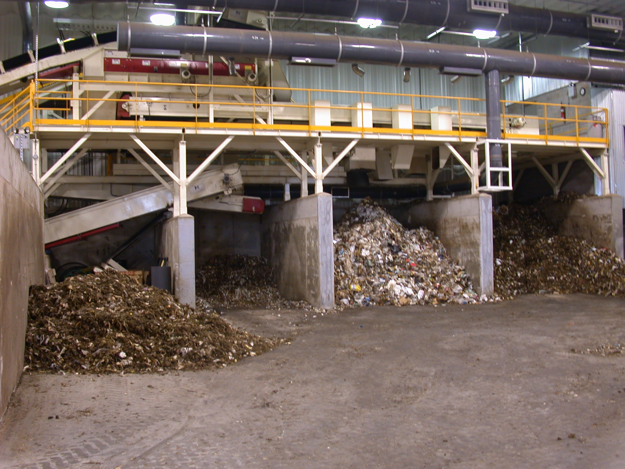 The feedstock is discharged into a holding bunker. Over 90% of the oversized materials removed by the star screen are cardboard, box board, or wood which are conveyed to a shredder. The shredded materials are discharged into a separate holding bunker for use as bulking materials.Additional bunkers for homogeneous organics and amendment materials are also provided in the Receiving Building. -