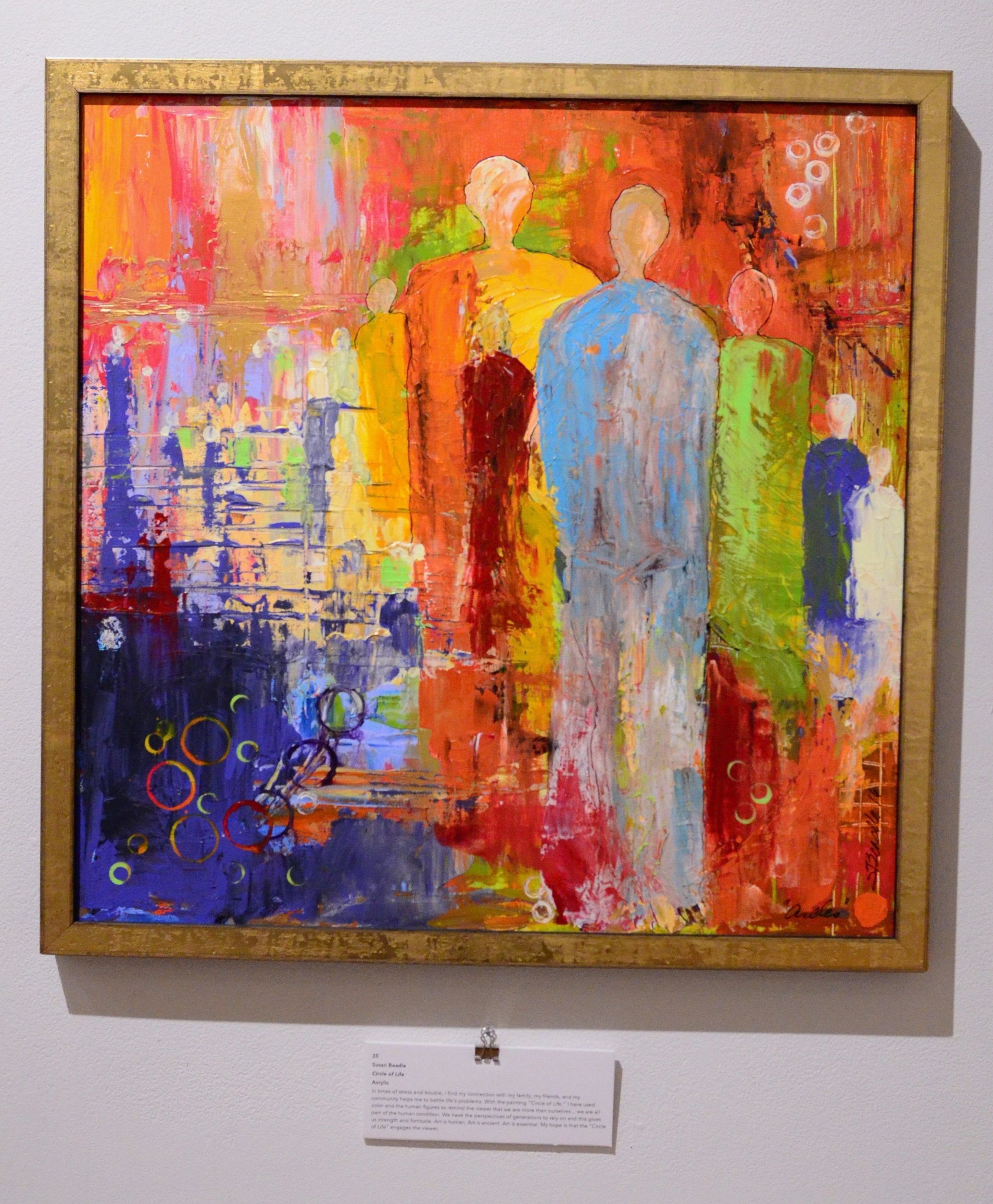 Circle of Life by Susan Beadle. Acrylic peice. Red and orange tones coat the top of the piece and create the bottom right portion of the background. Human figures span across the right side of the image. Deep and dark blue tones complete the bottom left corner of the background. Serious illness and caregiver