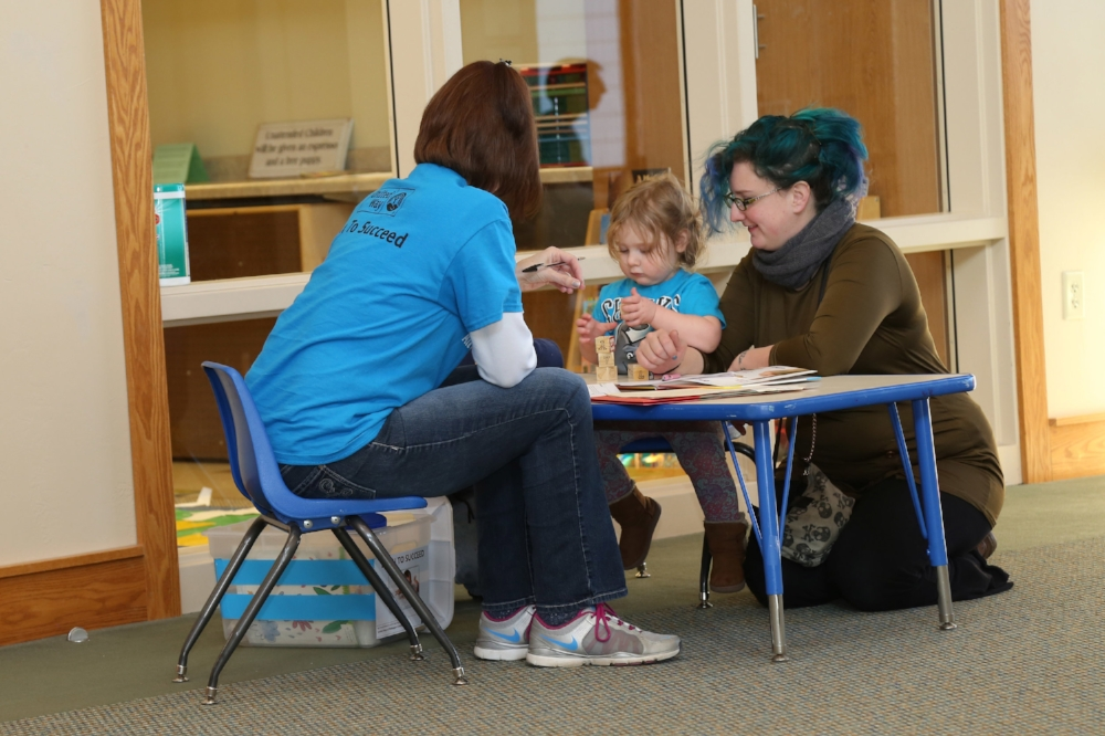 Staff working with a parent and child on developmental approrpiate activities