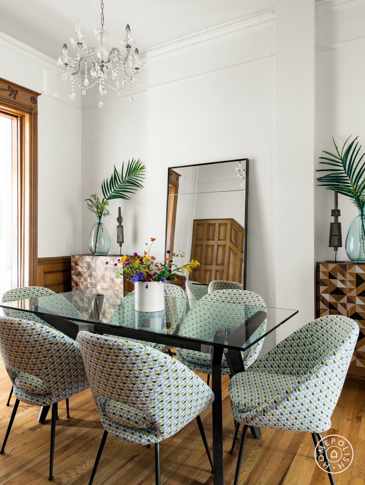 In the dining room, there are patterned chairs around a modern table sitting beneath a traditional crystal chandelier. The centerpiece of the living room is a vividly colorful rug, which is contrasted by neutral furnishings around it. It's bright but elegant; great for kids and guests. The den of this Brooklyn brownstone has plenty of storage for toys, a soft rug to play on the floor, fun bright art and patterns, (plus a great sofa for building forts).