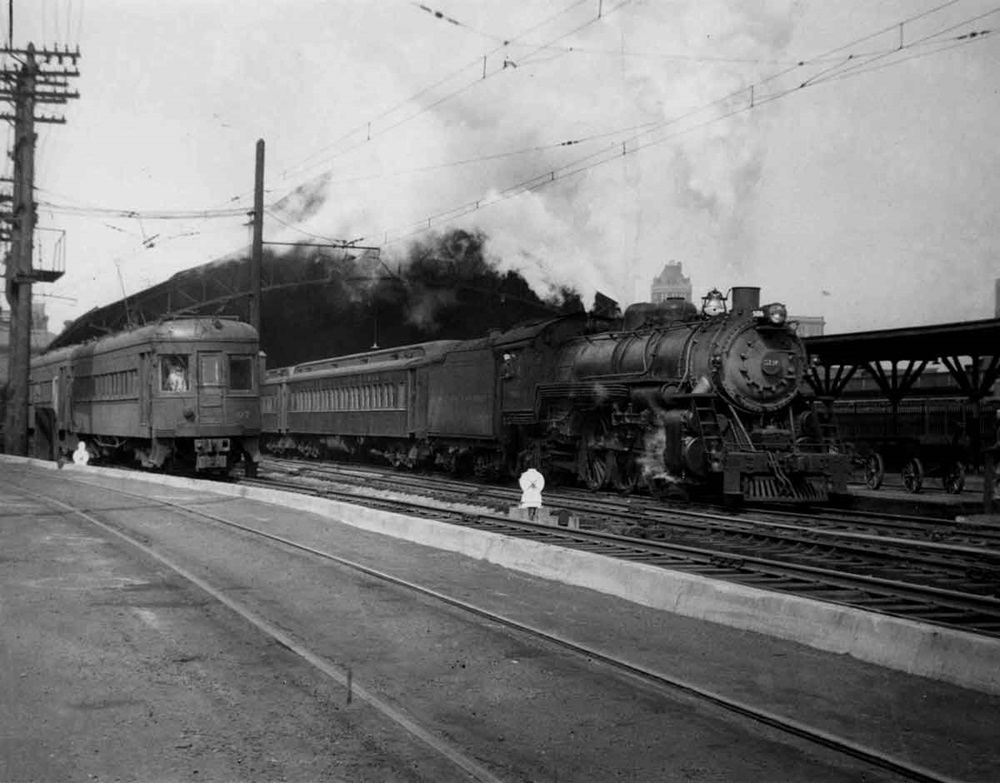 In a 1947 view at Baltimore & Ohio's Camden Station in Baltimore, a Baltimore & Annapolis interurban train #97 departs for Annapolis while a B&O 4-6-2 heads out with a train for Washington. B&A was a tenant at Camden until it shut down in 1950. Baltimore, Maryland Date: 1947. Source: Herbert H. Harwood Jr. Collection.