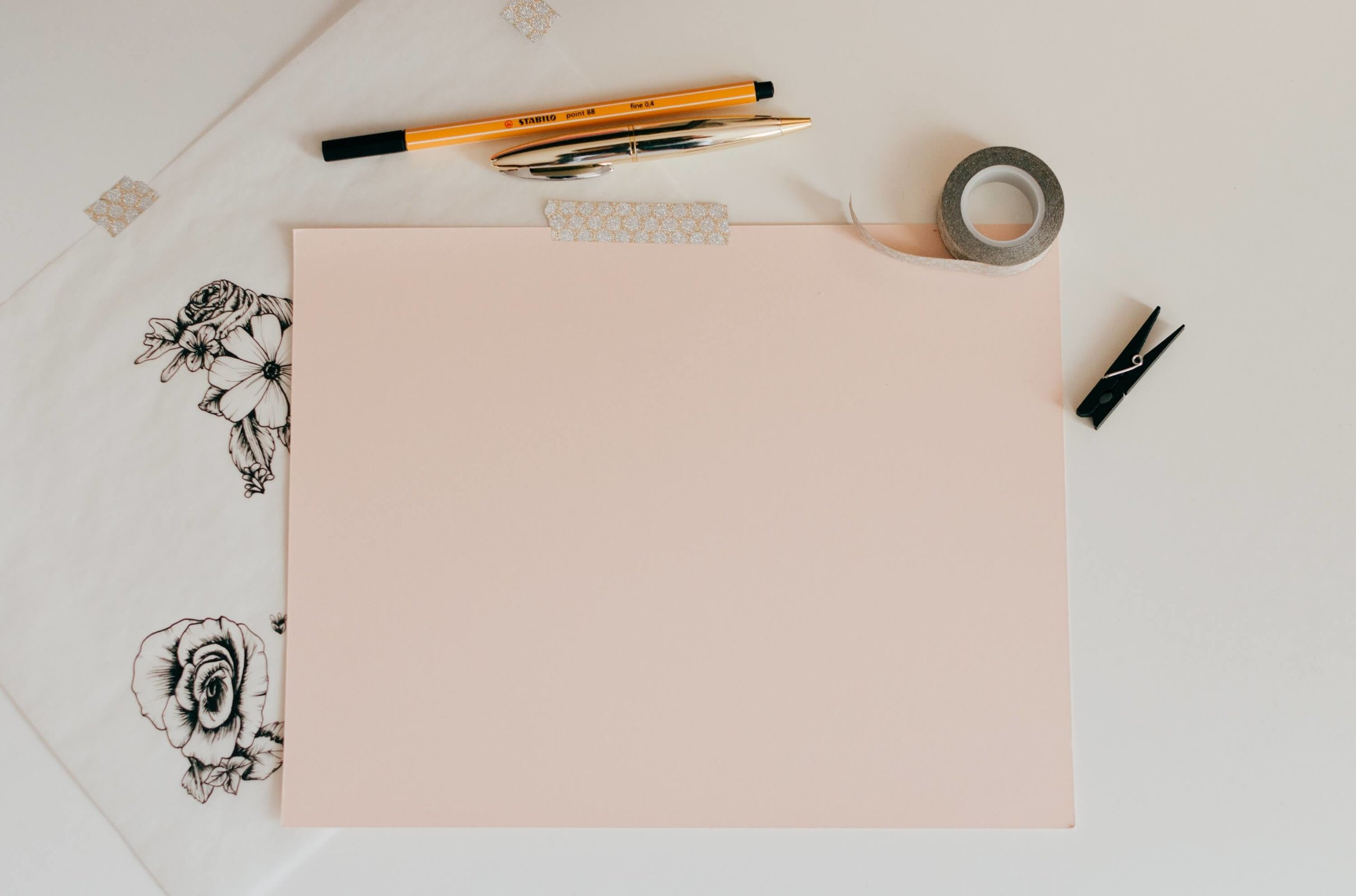 pink sheet of paper and office supplies
