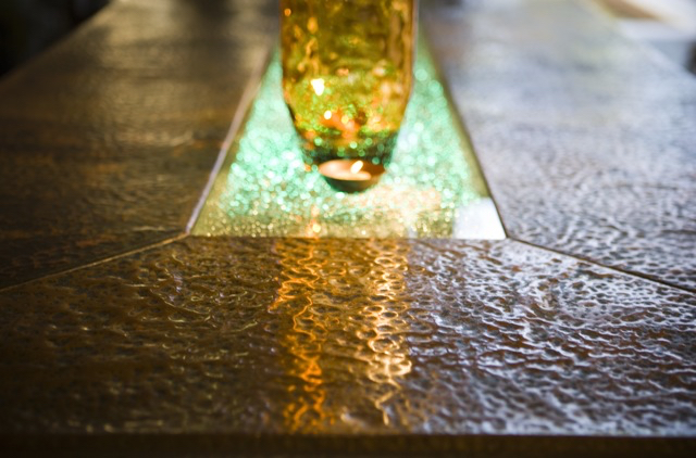 The copper table - Eventually SLH would begin to incorporate other materials into his designs. Although the base to this table continued the rustic theme at the Malibu property, the table top was wrapped in hand hammered copper, featuring layered tempered glass running down the centre of the table with the middle layer having been deliberately shattered giving the effect of a crystal when lit from below.