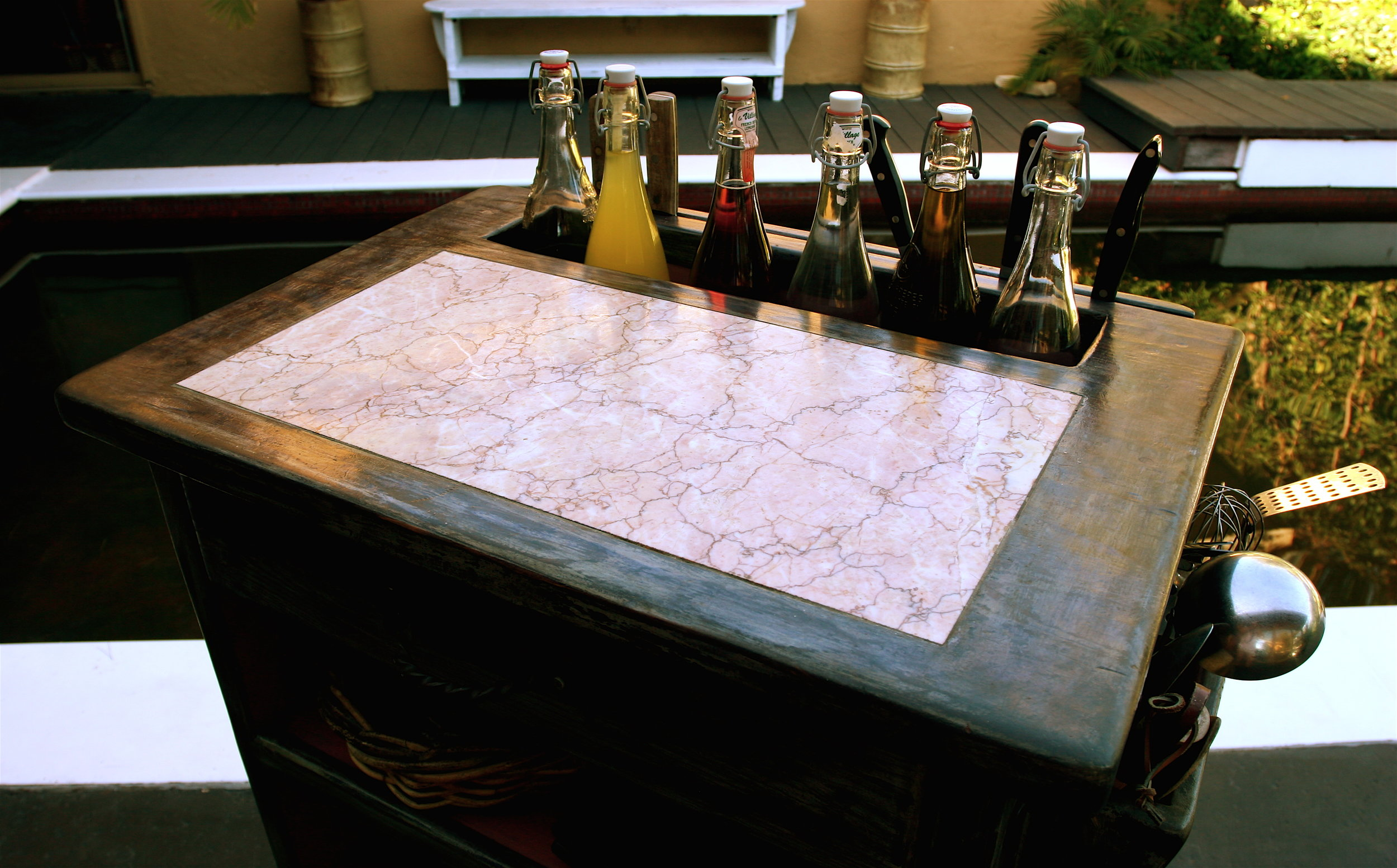 """A beautiful piece of pink marble from Spain was inset as a work surface to the kitchen cart. You can also see from this viewpoint the """"bottle well"""" which houses oils and vinegars for salads etc."""