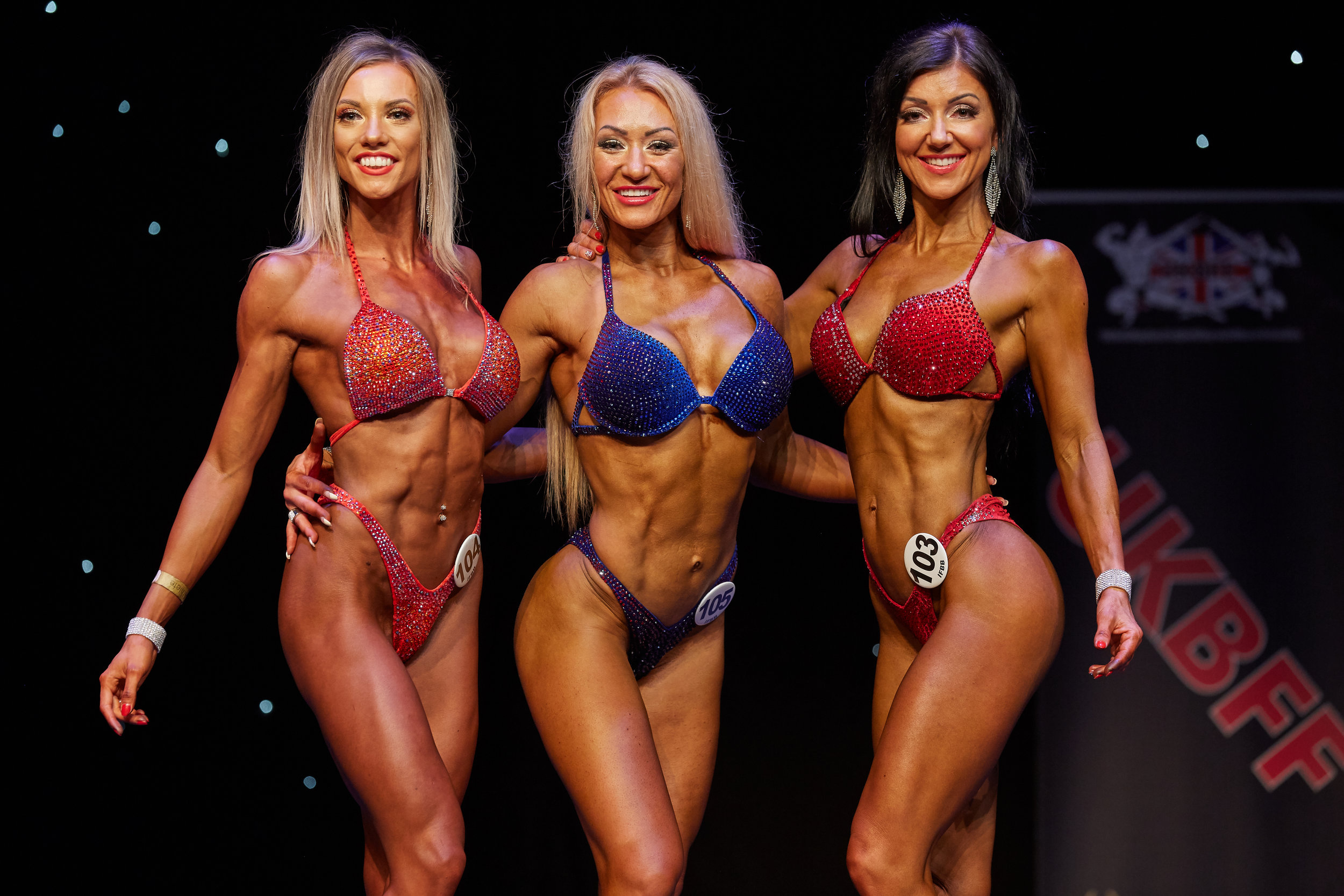 Ernestina Portnaja wins bikini fitness up to 164 cm, flanked by 2nd place Szilvia Babinszki (right) and Alice Richardson, who was third.