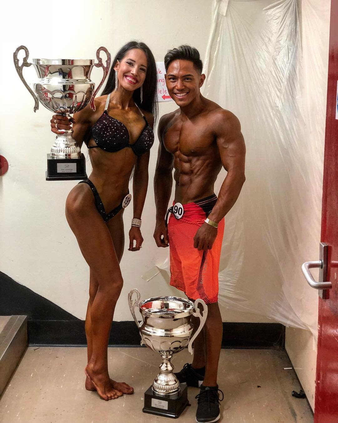 Marta Mila and El Noval, last year's bikini fitness and men's physique overall champions, pose backstage with their trophies.